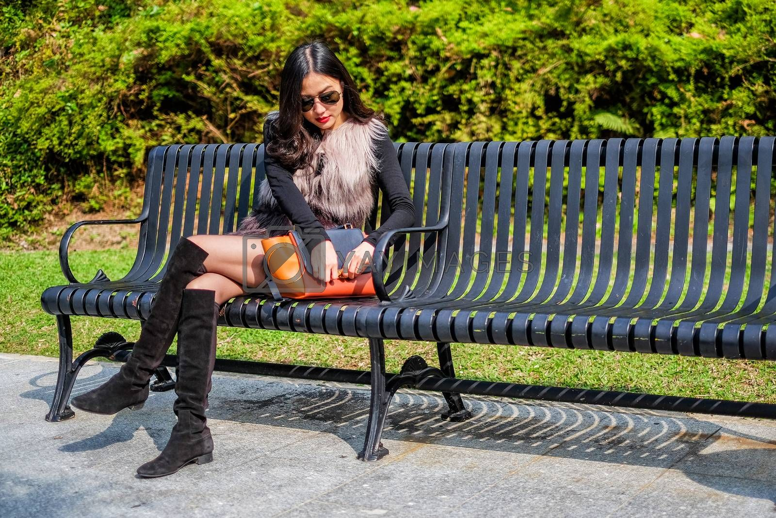Beautiful young woman sunglass resting in park