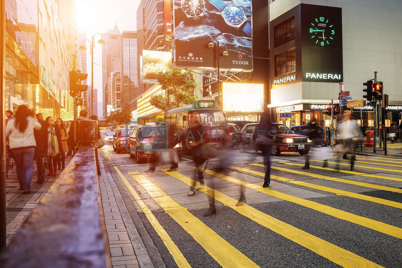 HONG KONG - JANUARY 14: People walking across Road, Causeway Bay in front of a big department store at Daylight. Hong Kong January 14, 2016