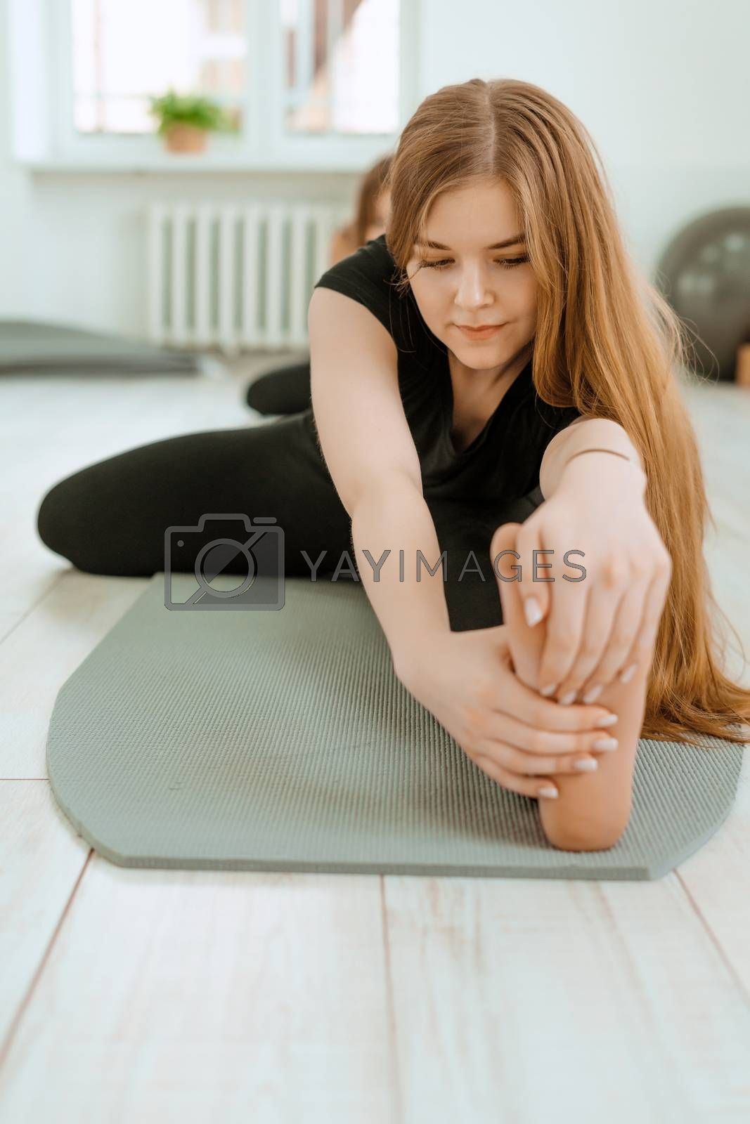 Stretching workout. Healthy lifestyle. Young beautiful girl in black uniform is doing stretching exercise. Akroyoga, yoga, fitness, workout, sport