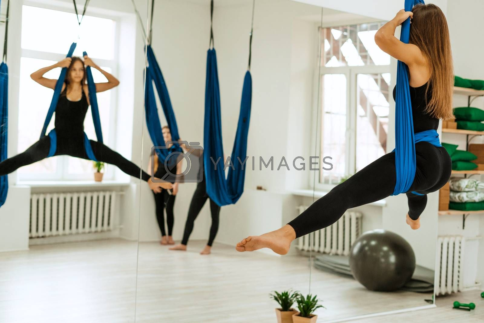 Stretching workout. A group of young girls in black uniforms are doing stretching training in the gym. Akroyoga, yoga, fitness, workout