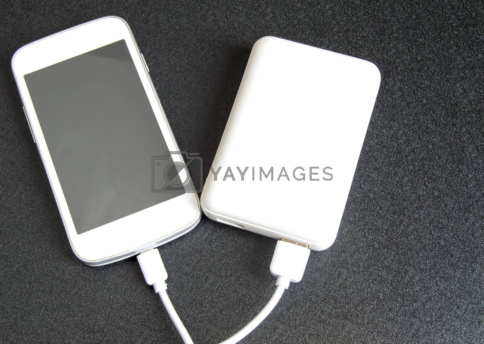 A white phone with a black screen and a copy of space is charged using a white power Bank. Top view, black background.
