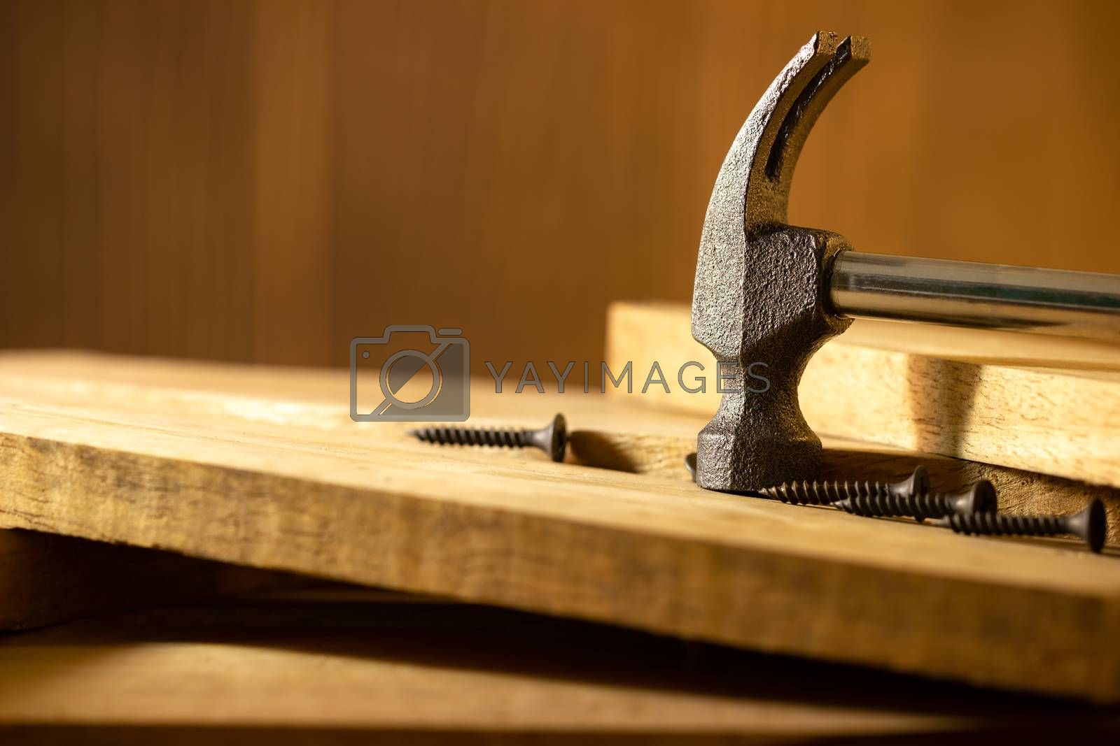 Hammer and screw on lumber in lighting and shadow of the sunshine in morning. The concept of woodcraft or carpentry.