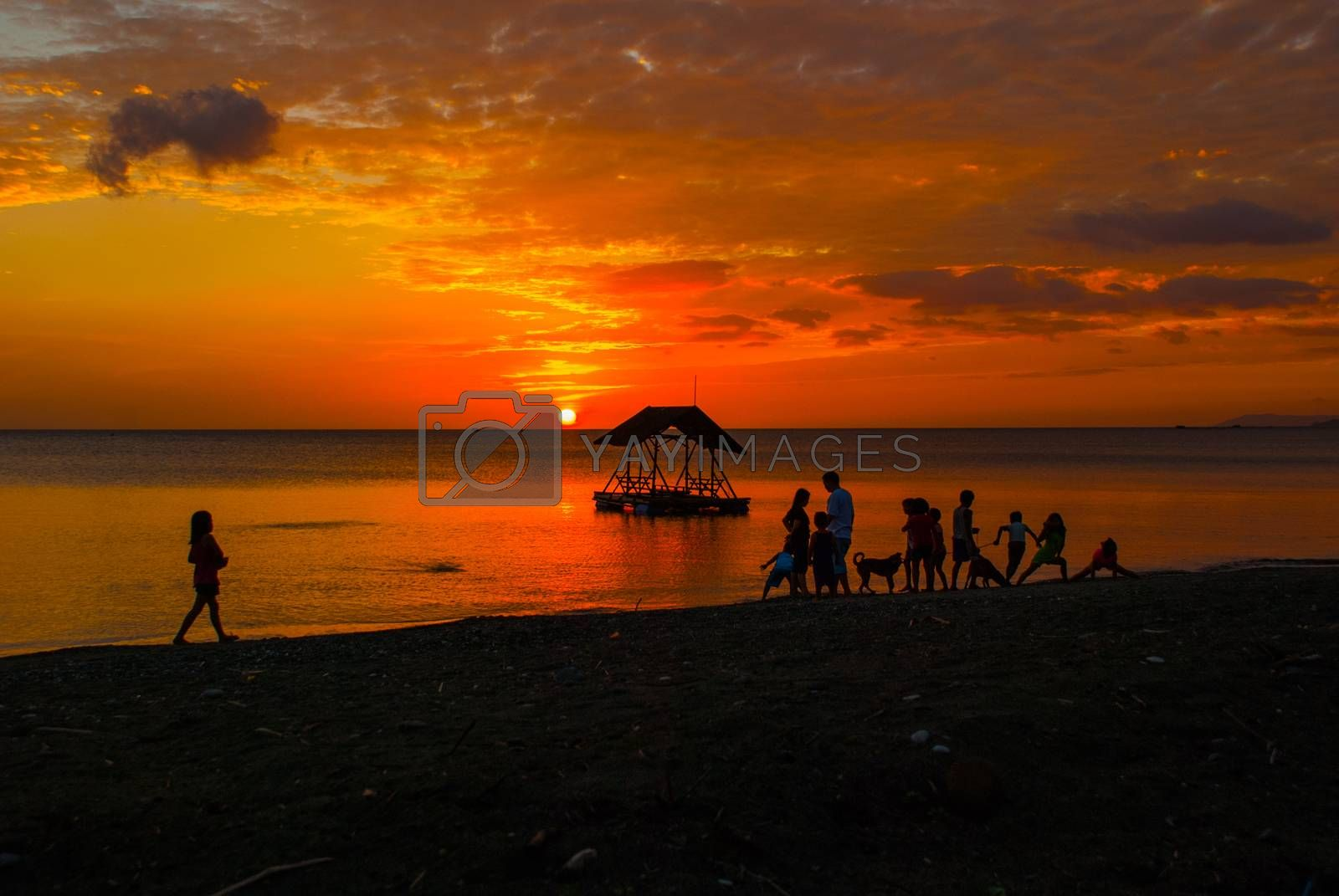 Beautiful sunset on the beach. Silhouettes of pavilions and people. Pandan, Panay island, Philippines
