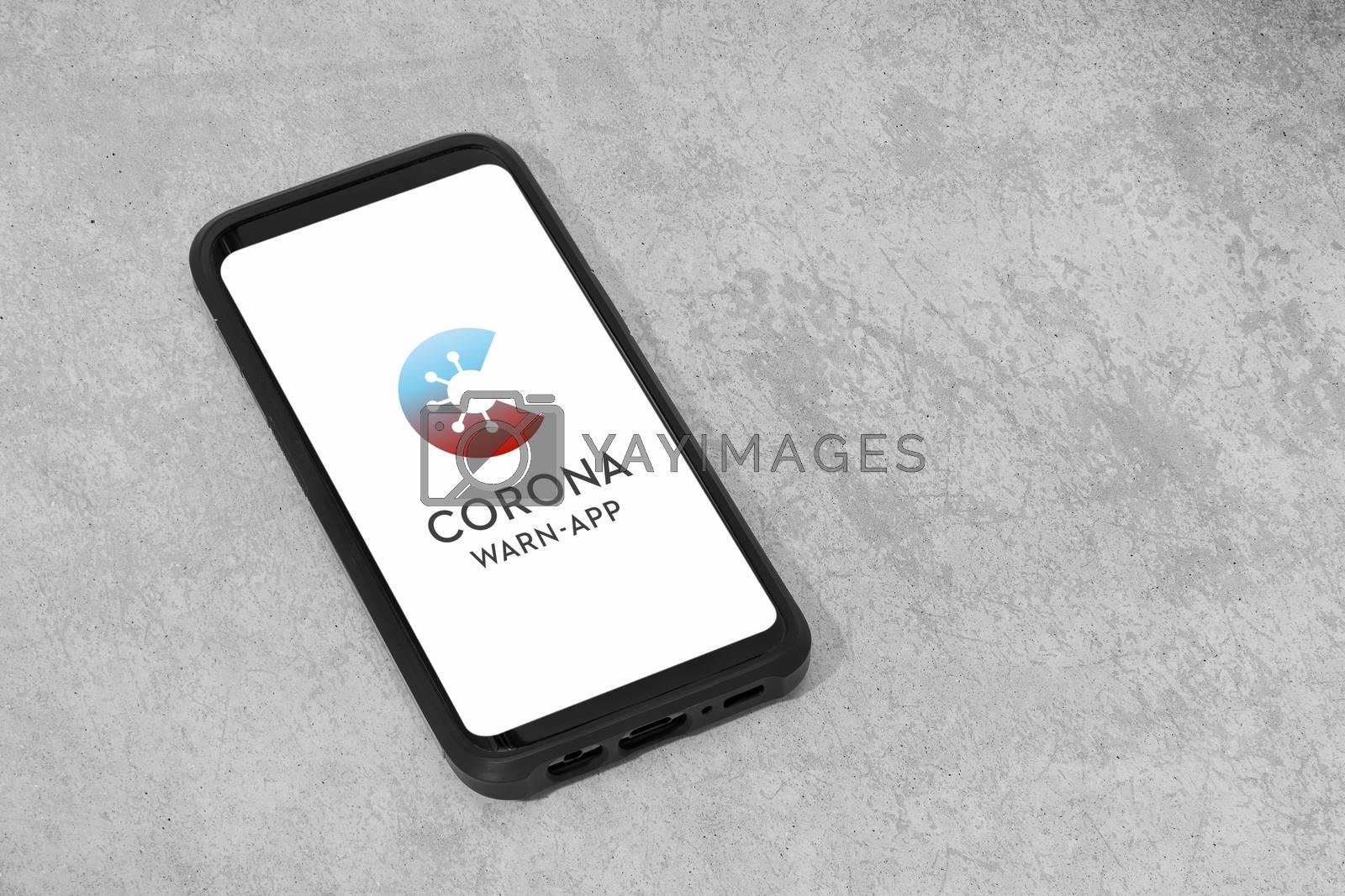 Galicia, Spain; june 18, 2020: German Corona Warn App in mobile phone on grunge concrete background. Copy space