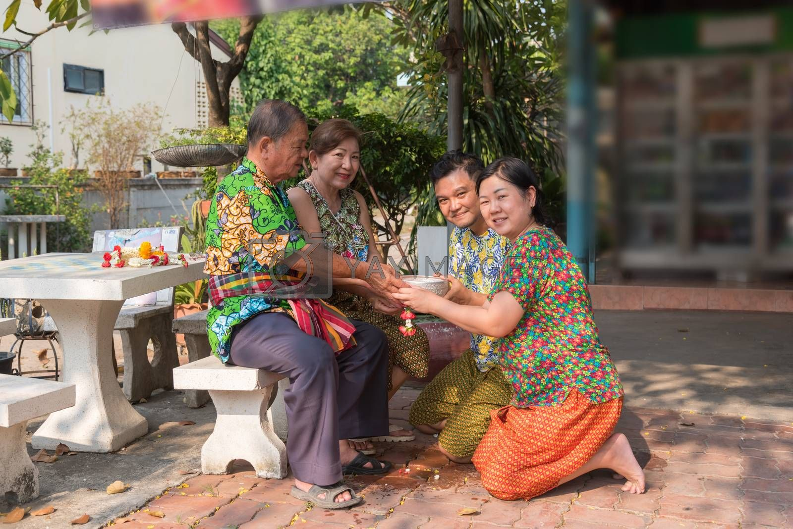 Asian young bathe with respect to parents by water have a jasmine and rose flower and aromatherapy in water in water bowl in Songkran Festival