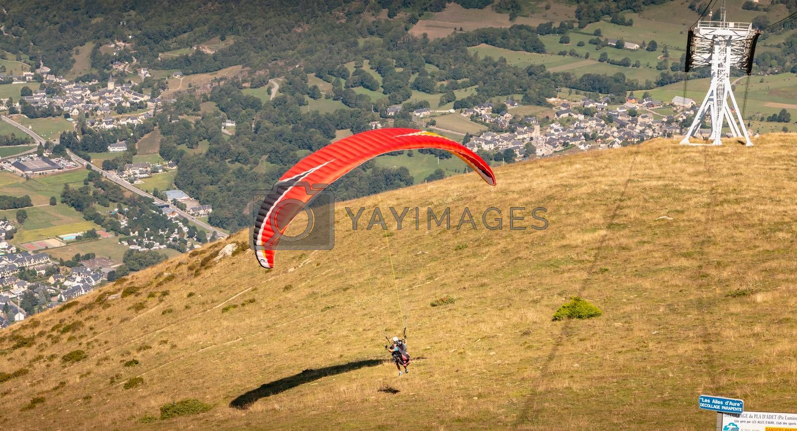 Saint Lary Soulan, France - August 20, 2018: takeoff of a paraglider from the top of the mountain, at 1700 meters altitude to fly over the valley on a summer day
