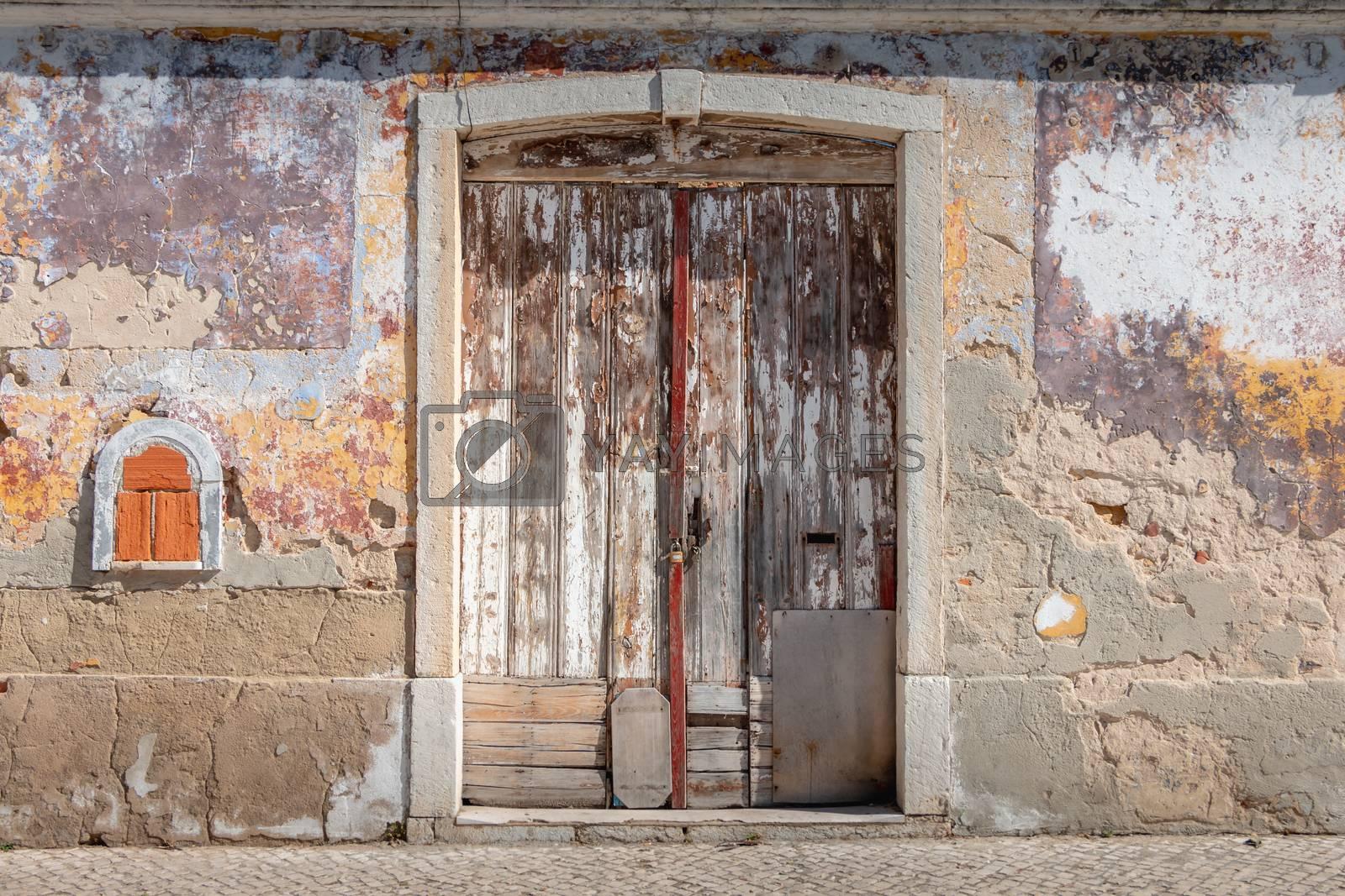 very old worn wooden door with peeling paint in portugal