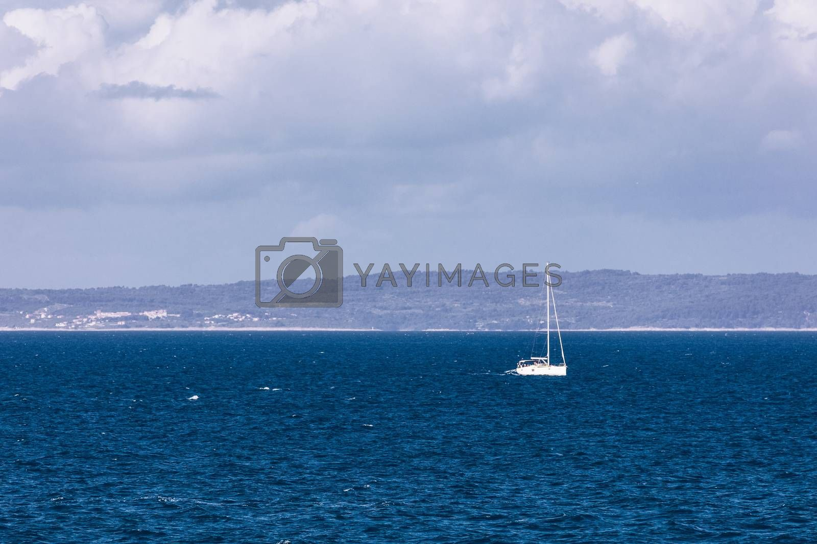 Sailboat in the sea in the evening sunlight with mountains background, luxury summer adventure, active vacation in Mediterranean sea, Croatia. Sailing ship luxury yacht with white sails in the Sea.