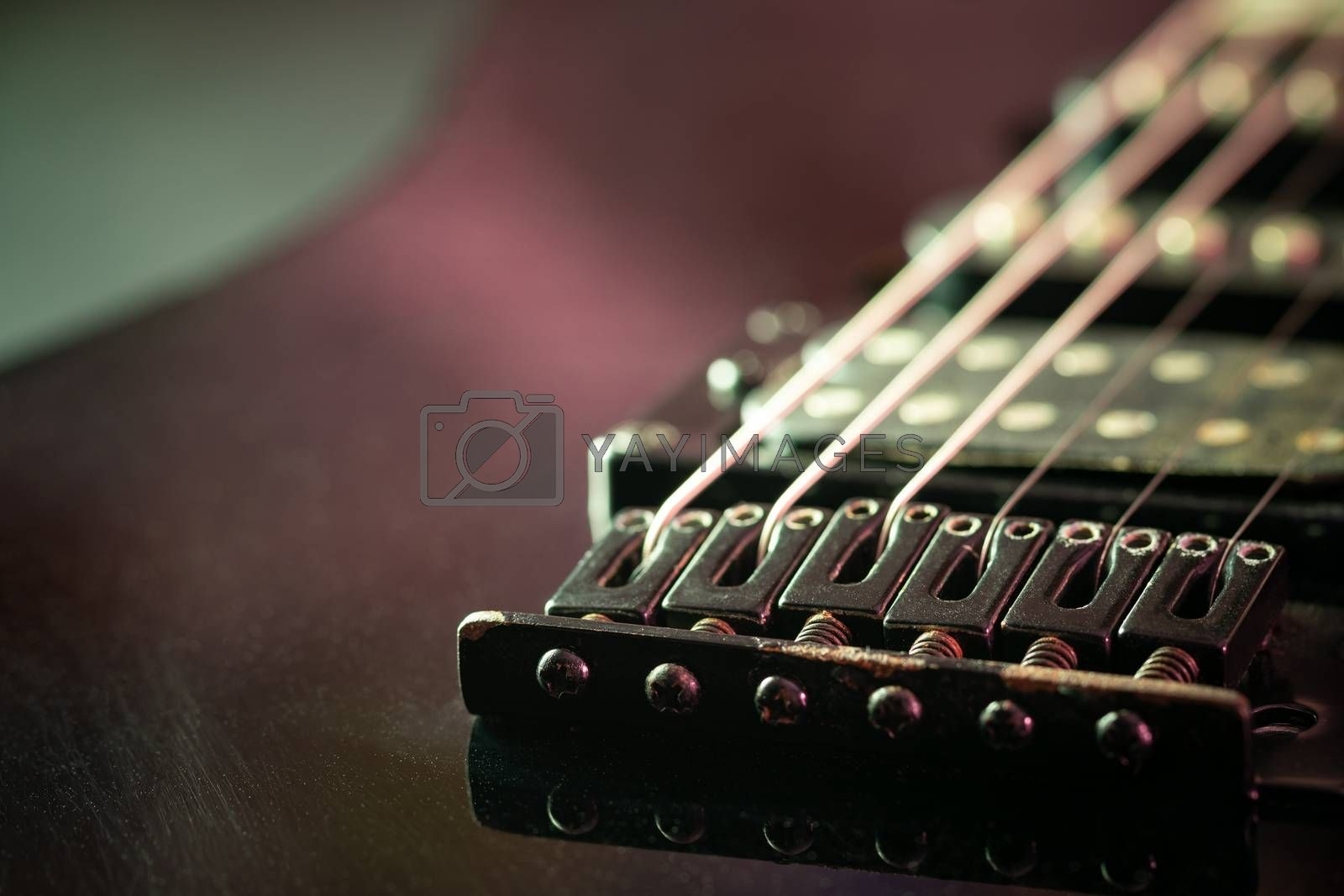 Rust bridge serves to fasten or tighten the string. Black vintage electric guitar in dark. Closeup and copy space. Concept of good memory About retro musical instruments and rock music.
