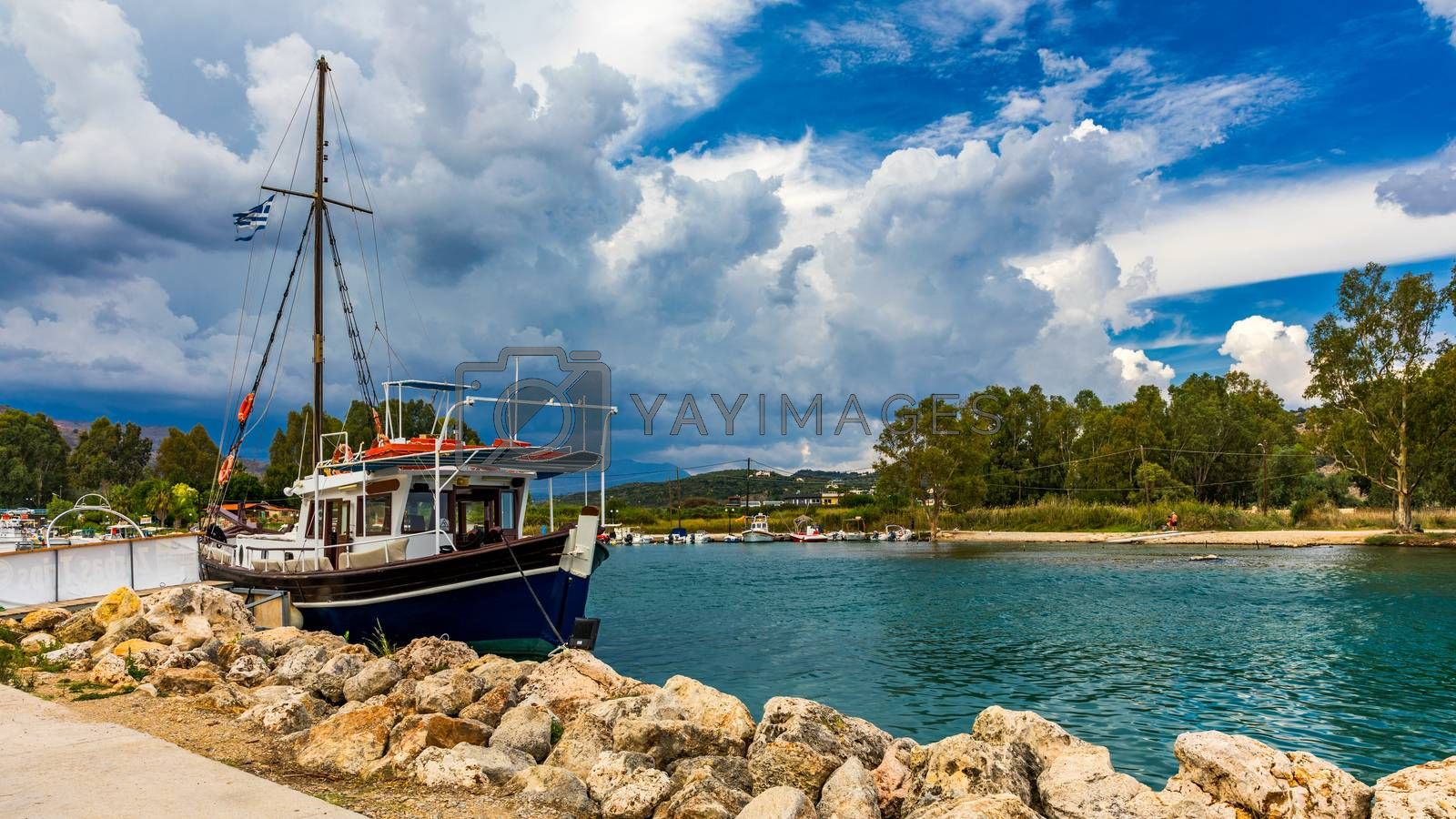 Georgioupoli is a resort village and former municipality in the Chania regional unit, Crete, Greece. Fishing boat in harbour Georgioupolis. Sea, ship and sky with clouds. River Almyros.