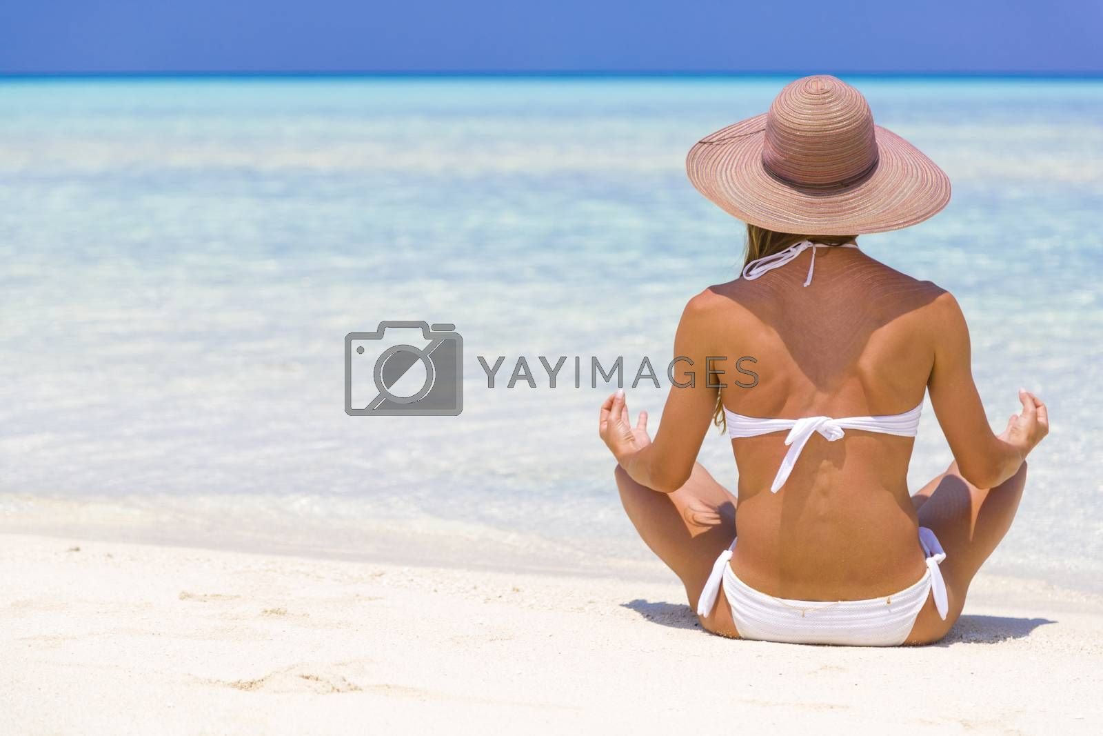 Young lady sitting on the shore in Maldives with straw hat meditating.