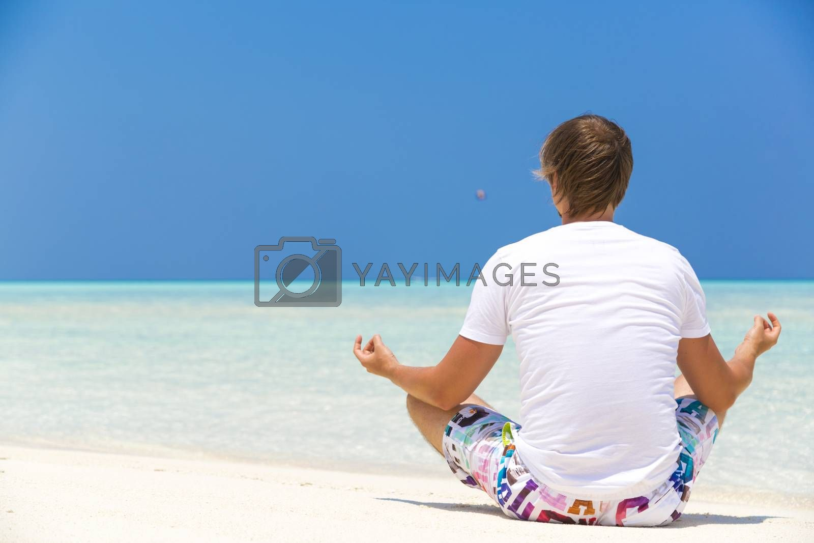 Man doing some relaxing exercises on the shore in Maldives.