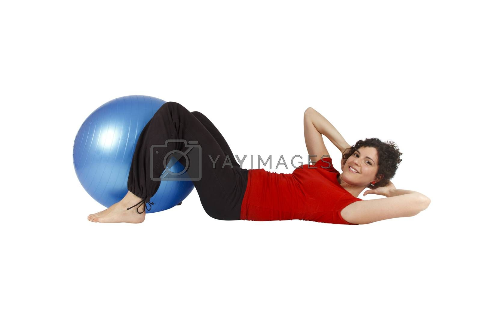 Young woman doing some sit-ups with a blue yoga ball.