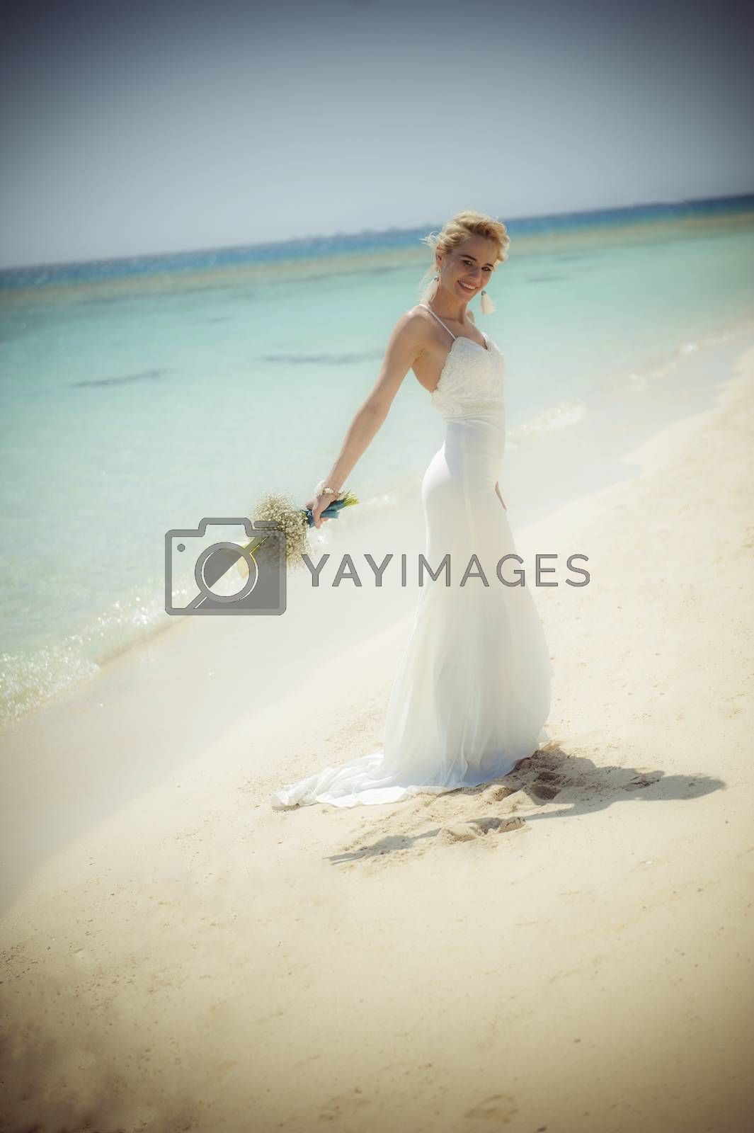 Beautiful woman bride at a tropical beach paradise on wedding day in white gown dress with ocean view vintage style photo