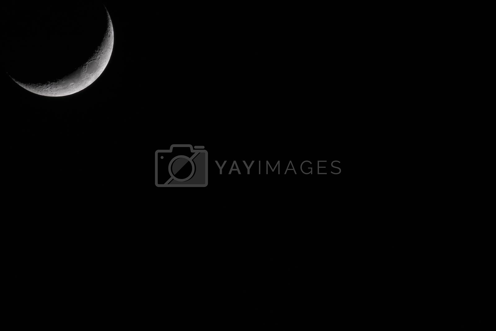 Crescent Moon against black sky at night with large copy space