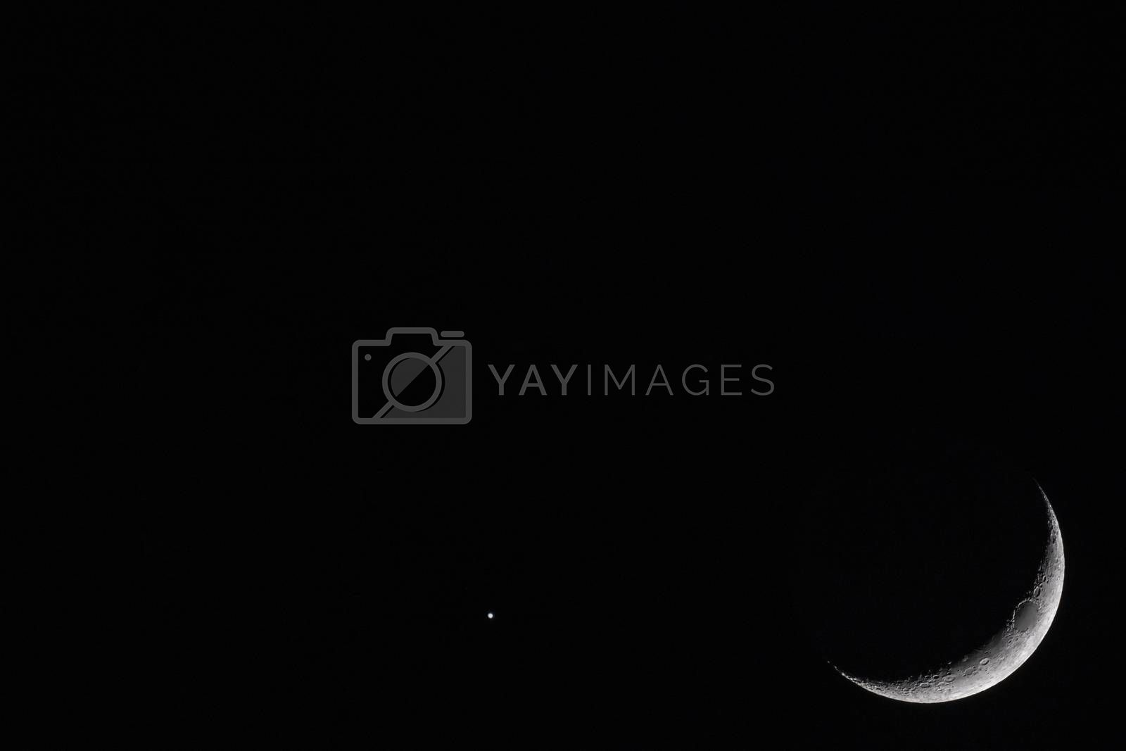 Crescent Moon with bright star against black sky at night with large copy space