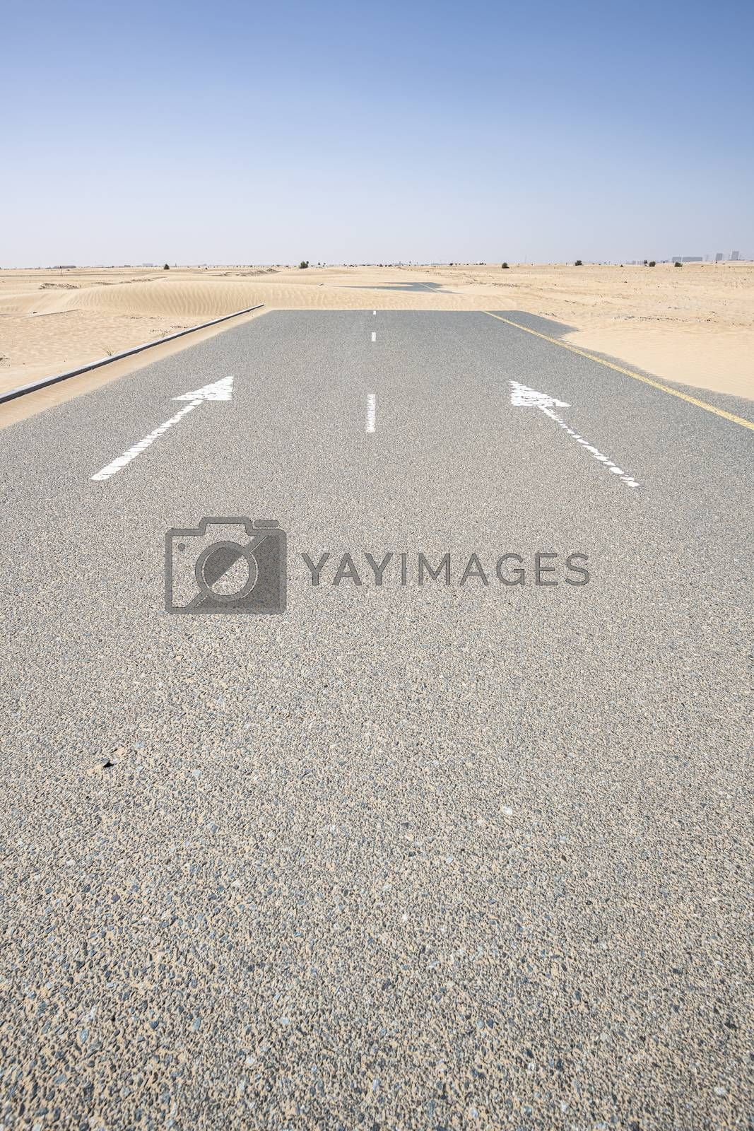 Vertical shot of an empty road covered by sand in the desert with blue sky. Large copy space on the tarmac