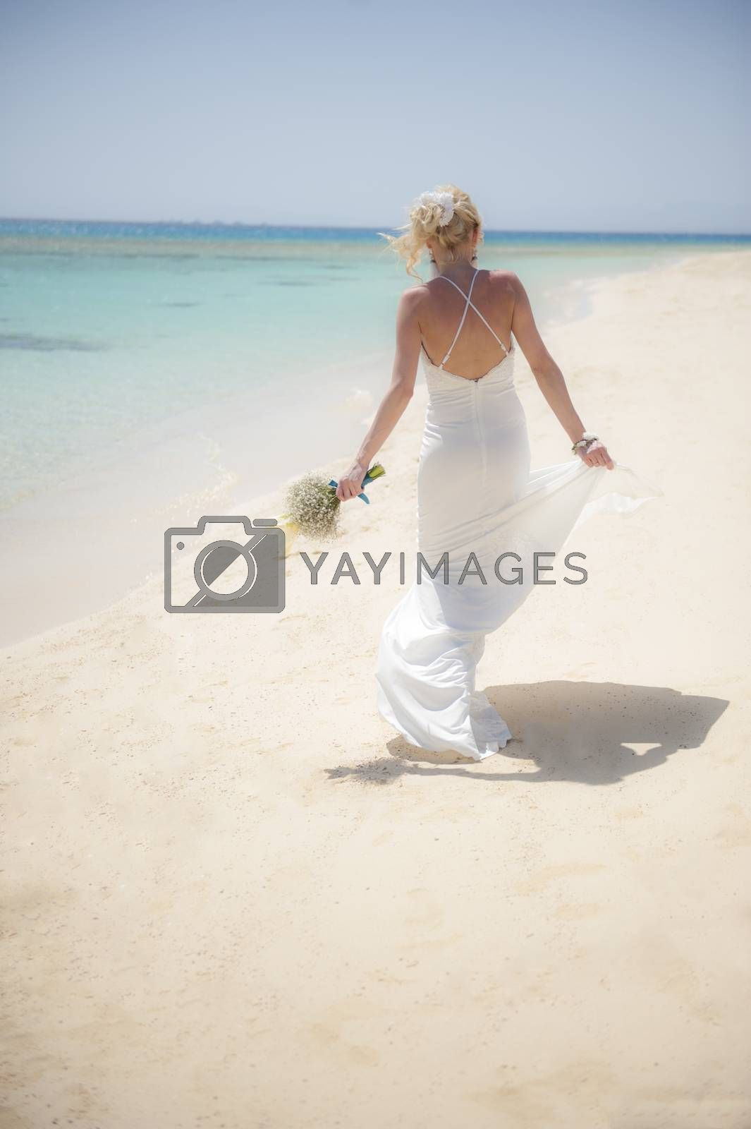 Beautiful woman bride at a tropical beach paradise on wedding day in white gown dress with ocean view