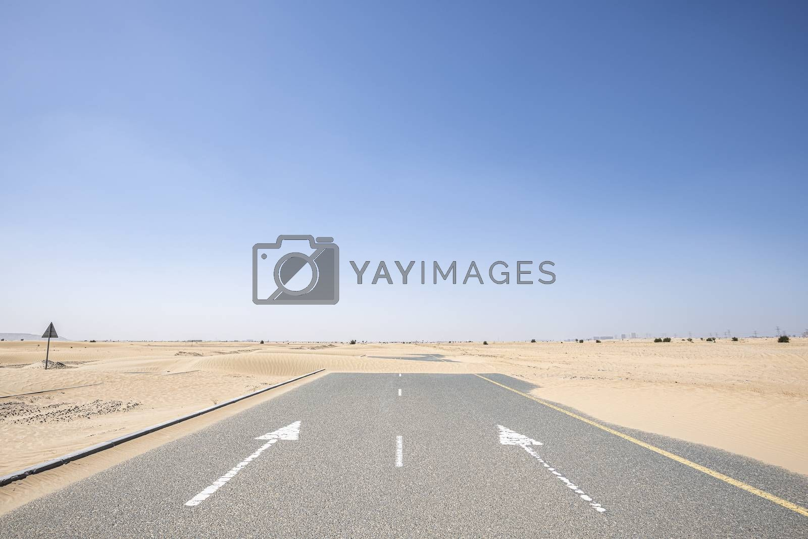 Horizontal shot of an empty road in the desert with large copy space in the blue sky