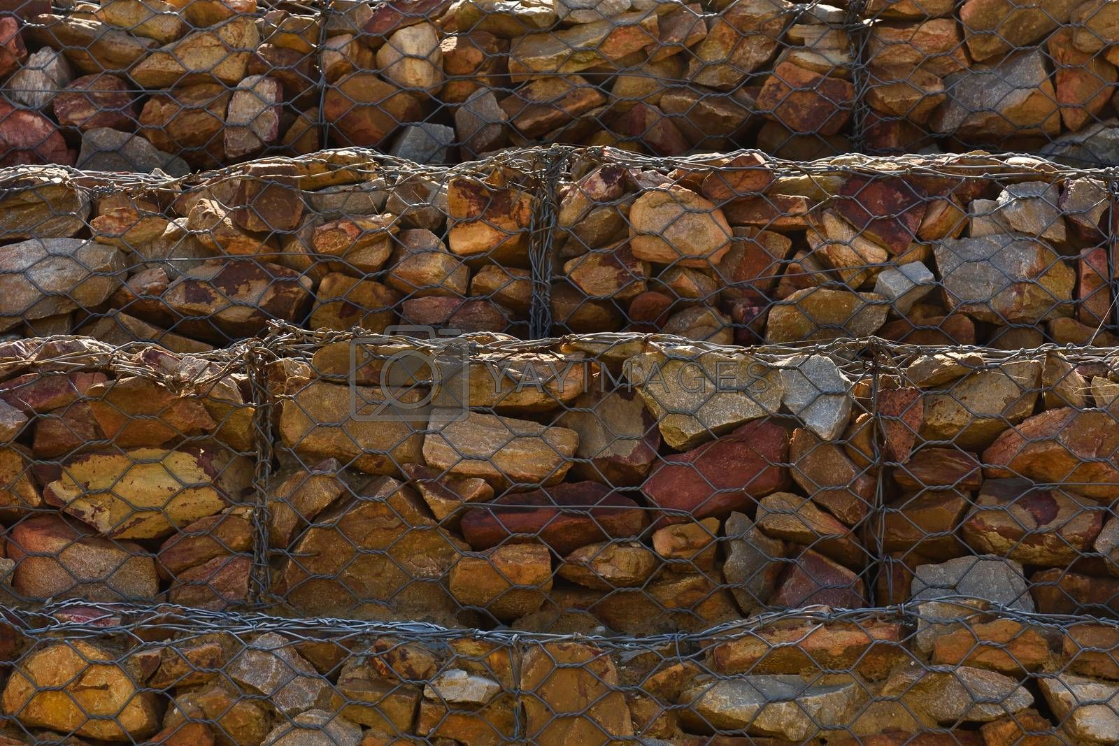 Close-up of a rock and mesh wire containment wall to stop hillside erosion, Mossel Bay, South Africa
