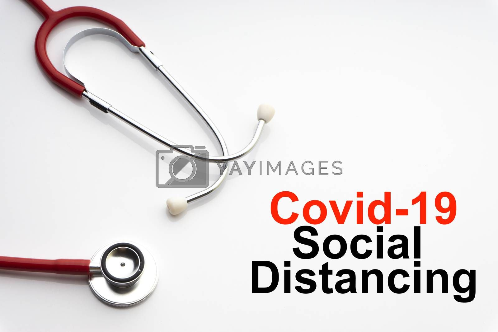 COVID-19 SOCIAL DISTANCING text with stethoscope on white background. Covid or Coronavirus Concept