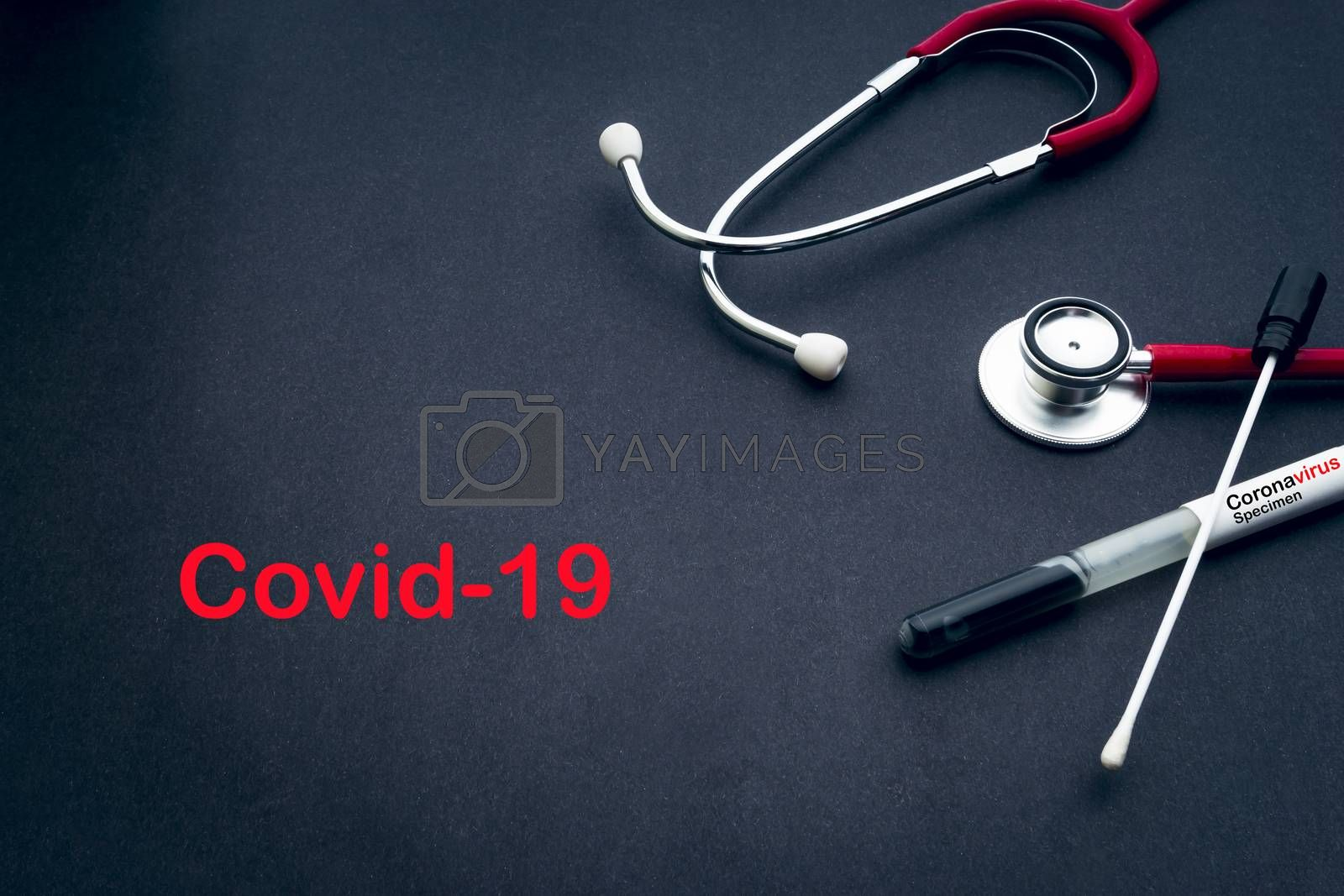 COVID-19 text with stethoscope and medical swabs on black background. Covid -19 or Coronavirus Concept
