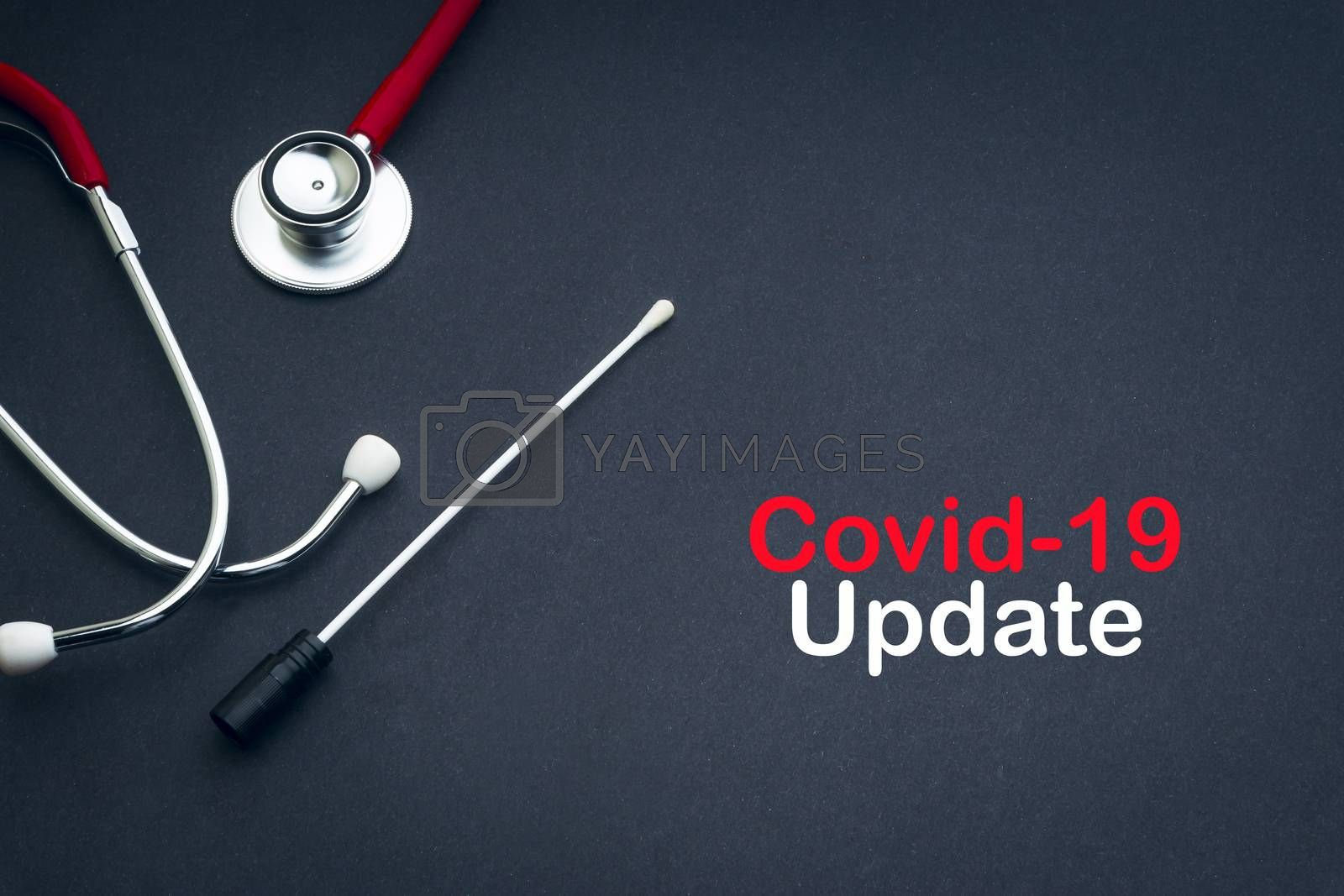 COVID-19 UPDATE text with stethoscope and medical swabs on black background. Covid -19 or Coronavirus Concept