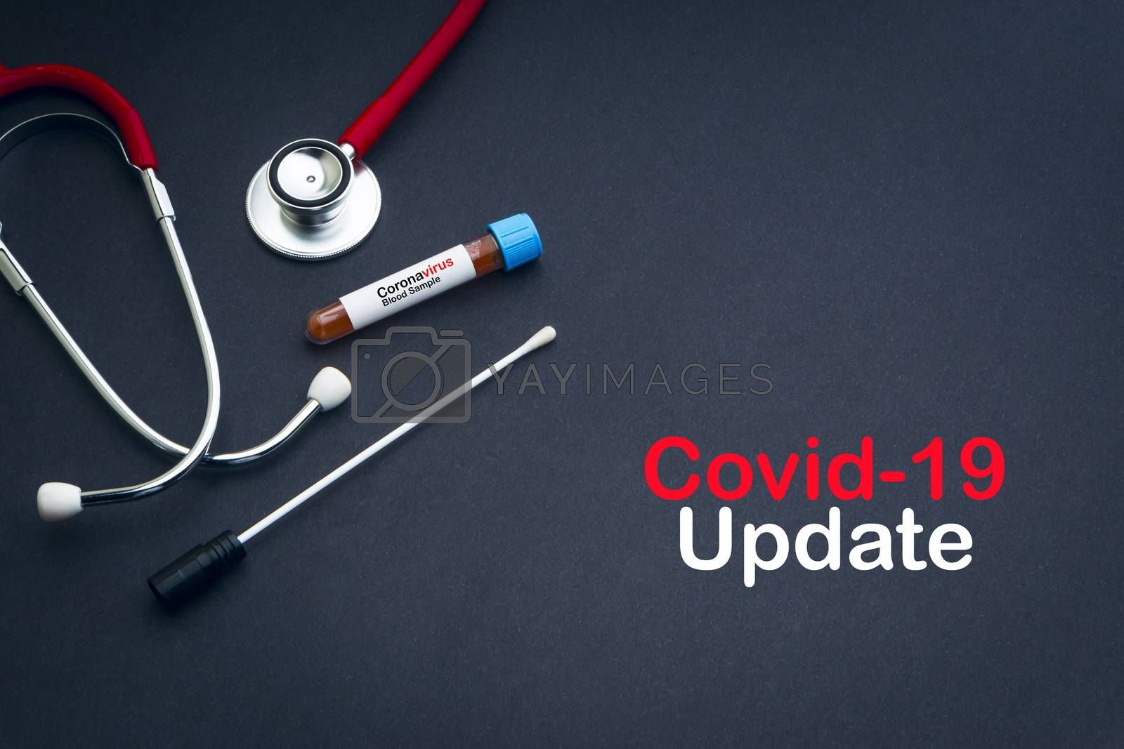 COVID-19 UPDATE text with stethoscope, blood sample vacuum tube and medical swabs on black background. Covid -19 or Coronavirus Concept