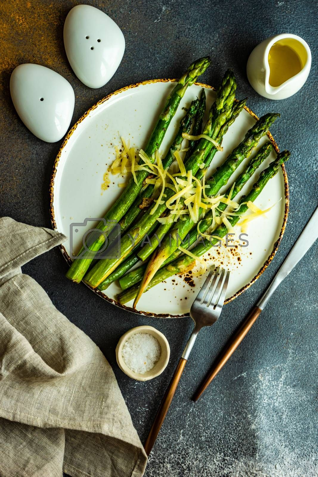 Organic grilled asparagus served for healthy keto lunch on stone background with copy space