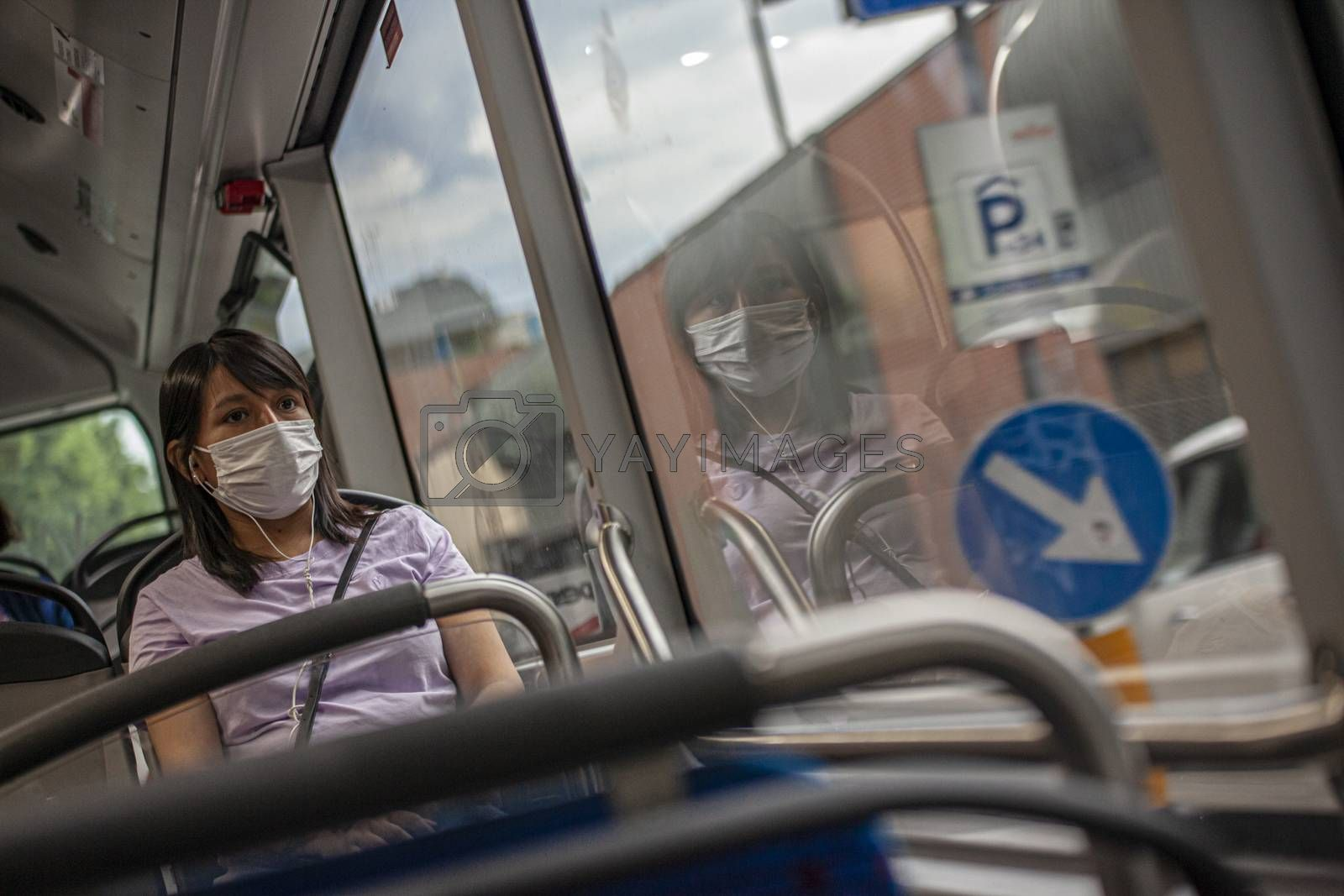 BOLOGNA, ITALY 17 JUNE 2020: Girl in the bus with medical mask during Covid quarantine