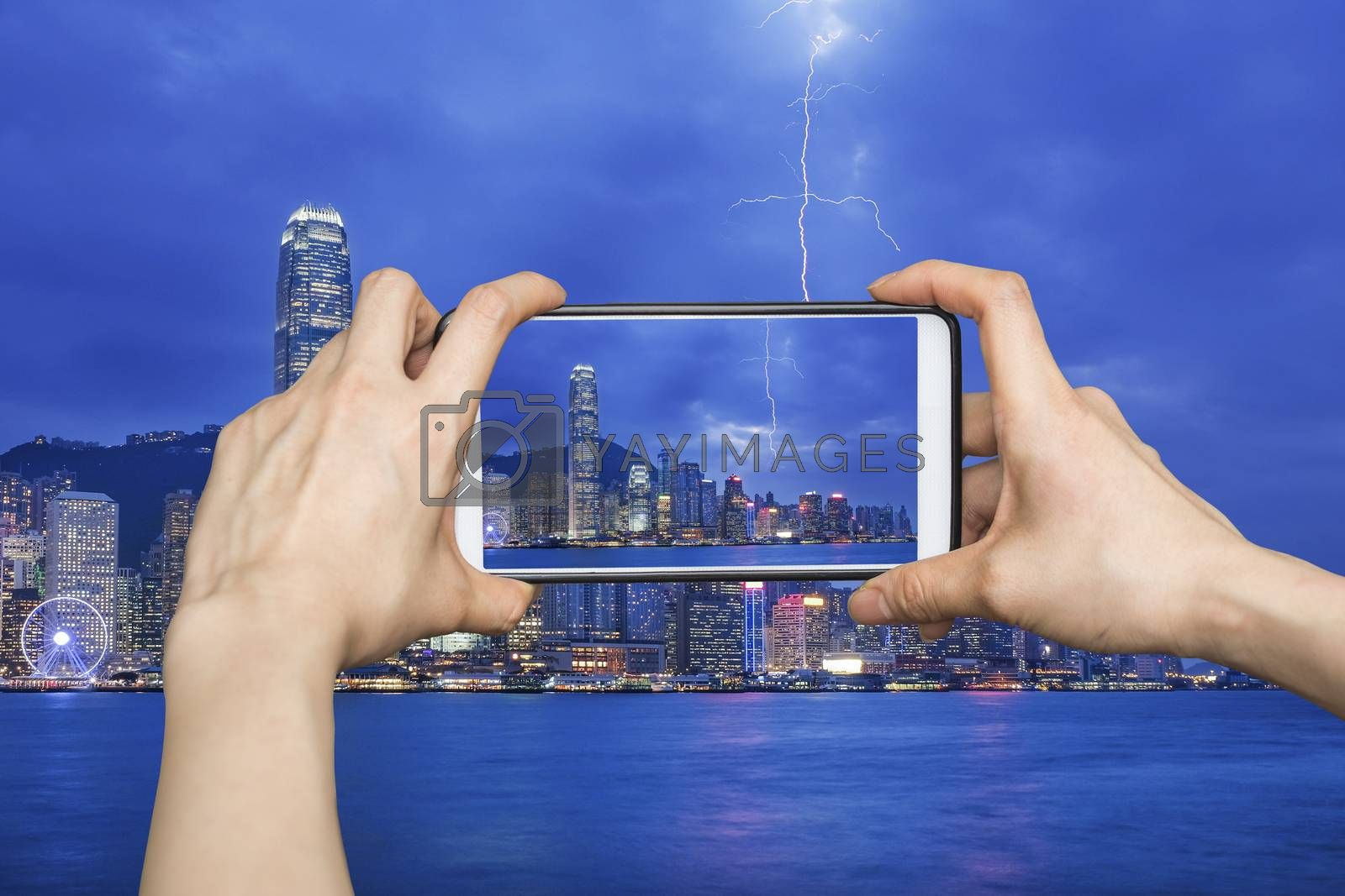 Girl taking pictures on mobile smart phone in Thunderstorm HongKong cityscape at night , Hong kong city.