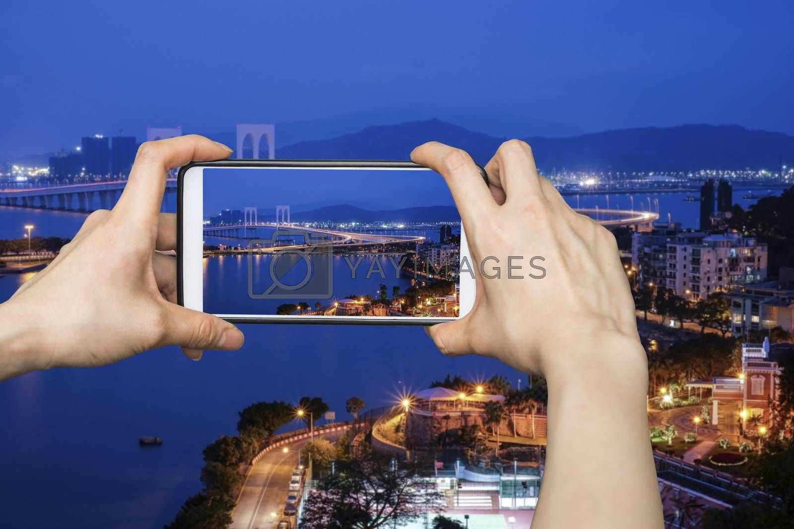 Girl taking pictures on mobile smart phone in View point Bridge in Macau at night