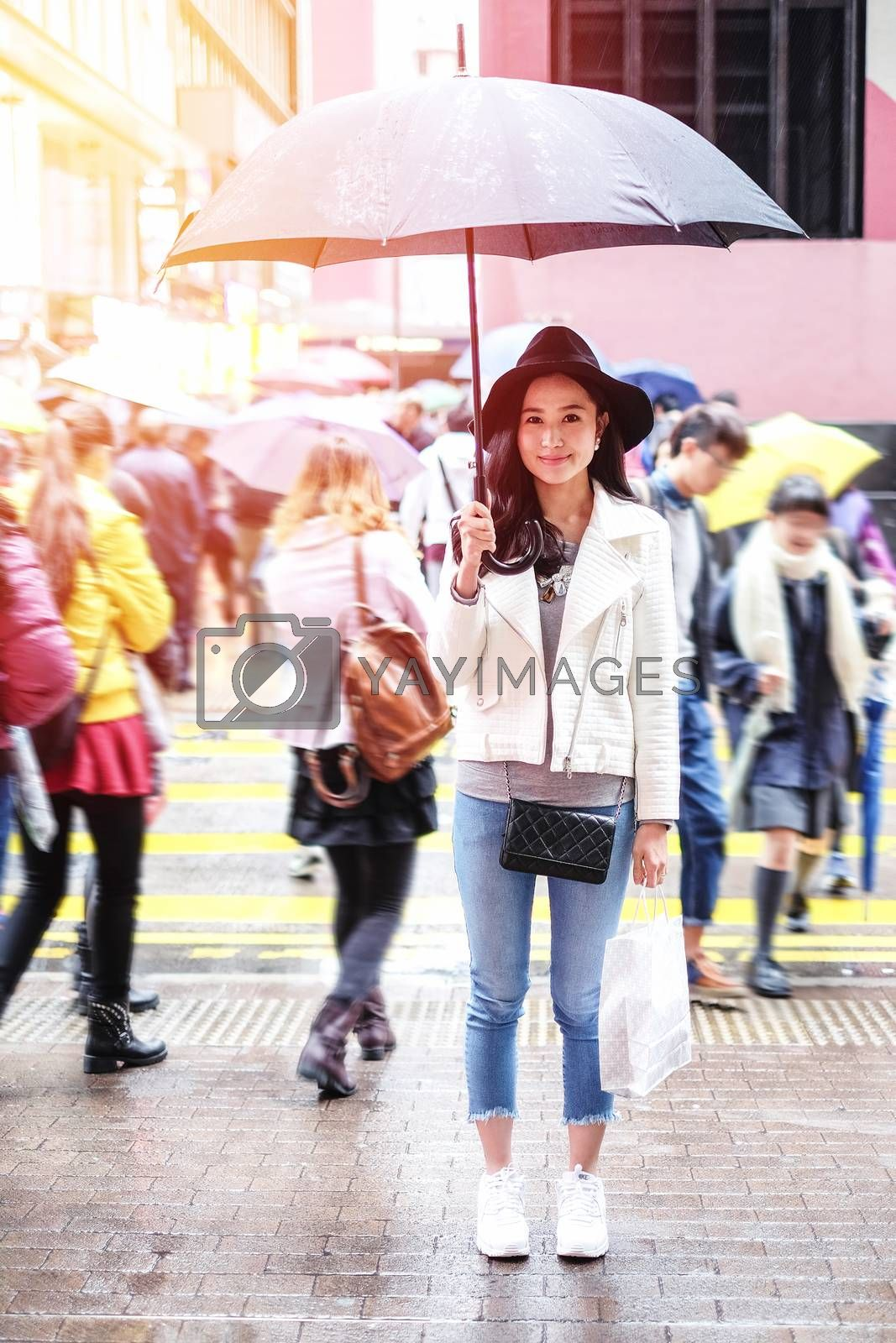 beautiful woman with shopping bags on the street in the rainny day