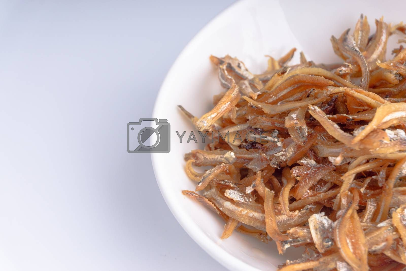 Fried anchovies in bowl close up with selective focus and crop fragment