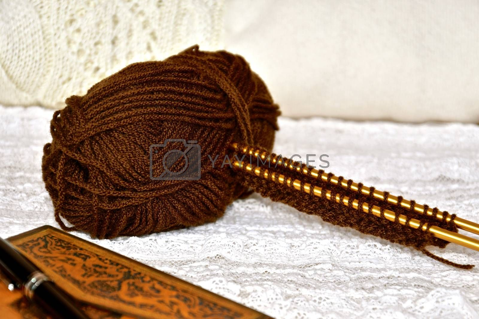 Concept of relaxation with knitting and journal in a still life composition with warm autumnal colours
