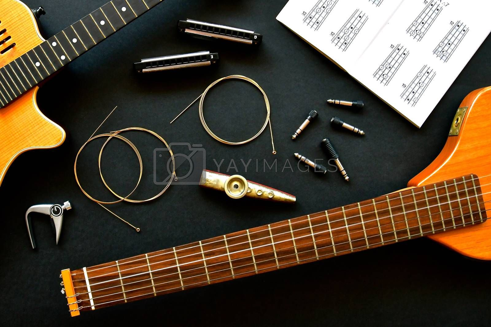 Music flatlay with an acoustic classical guitar, harmonicas, kazoo and coils of brass guitar strings.