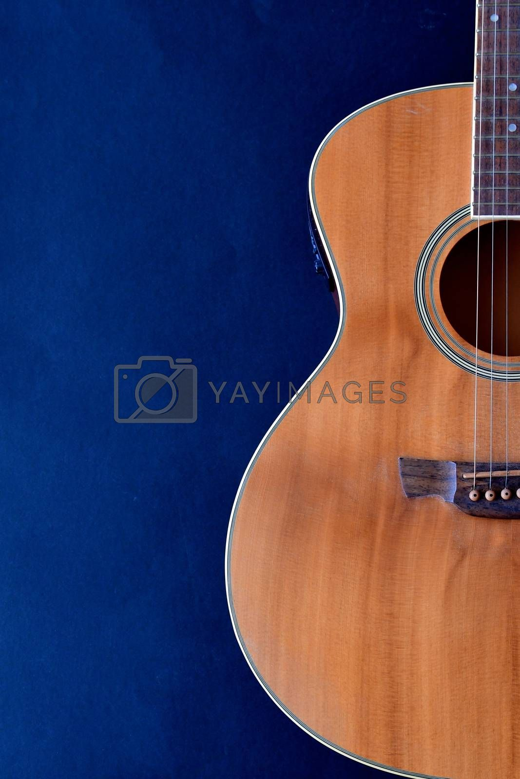Partial aerial view of the body of a wooden acoustic classical guitar isolated on a black background.