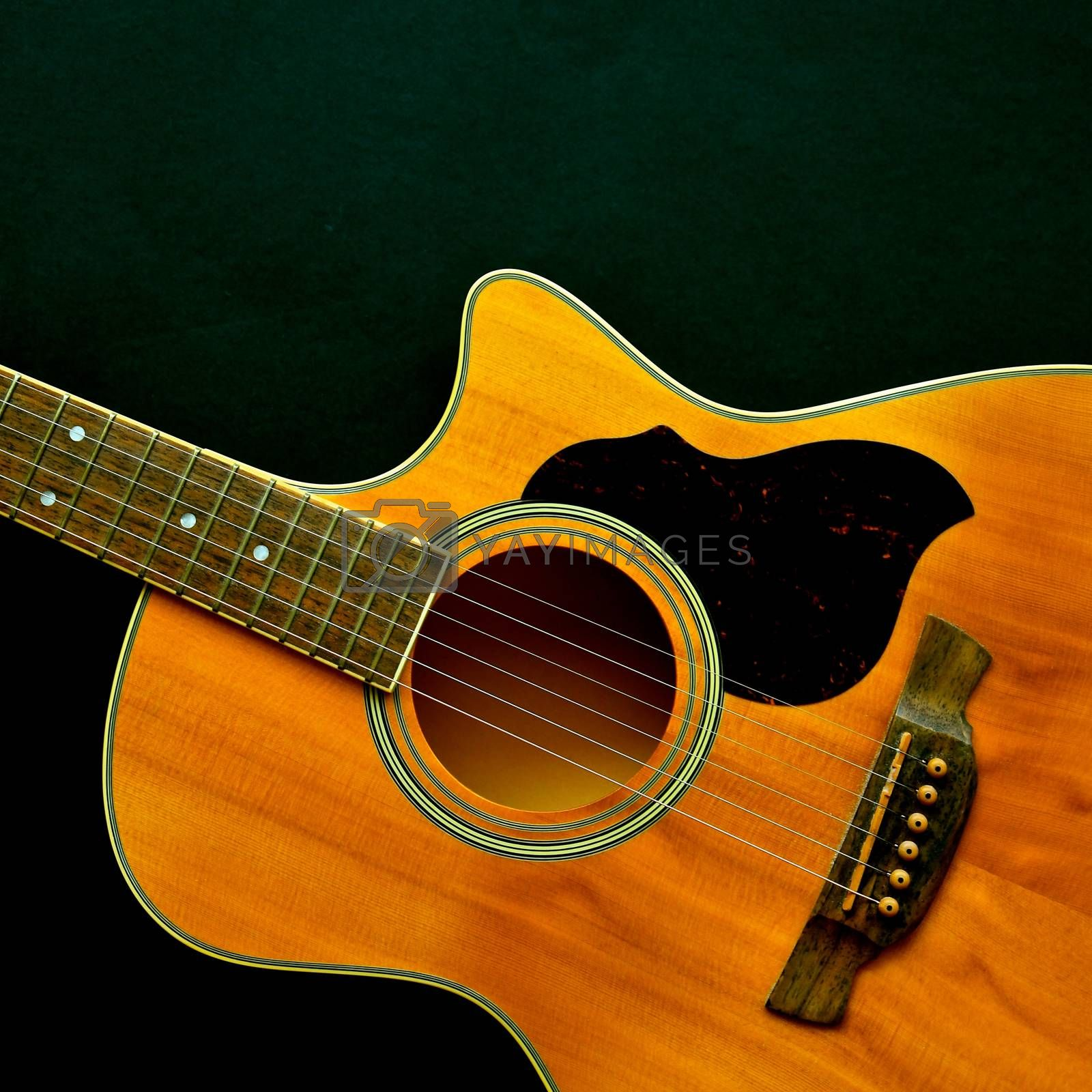 Aerial view of a wooden classical acoustic guitar isolated on a black background.
