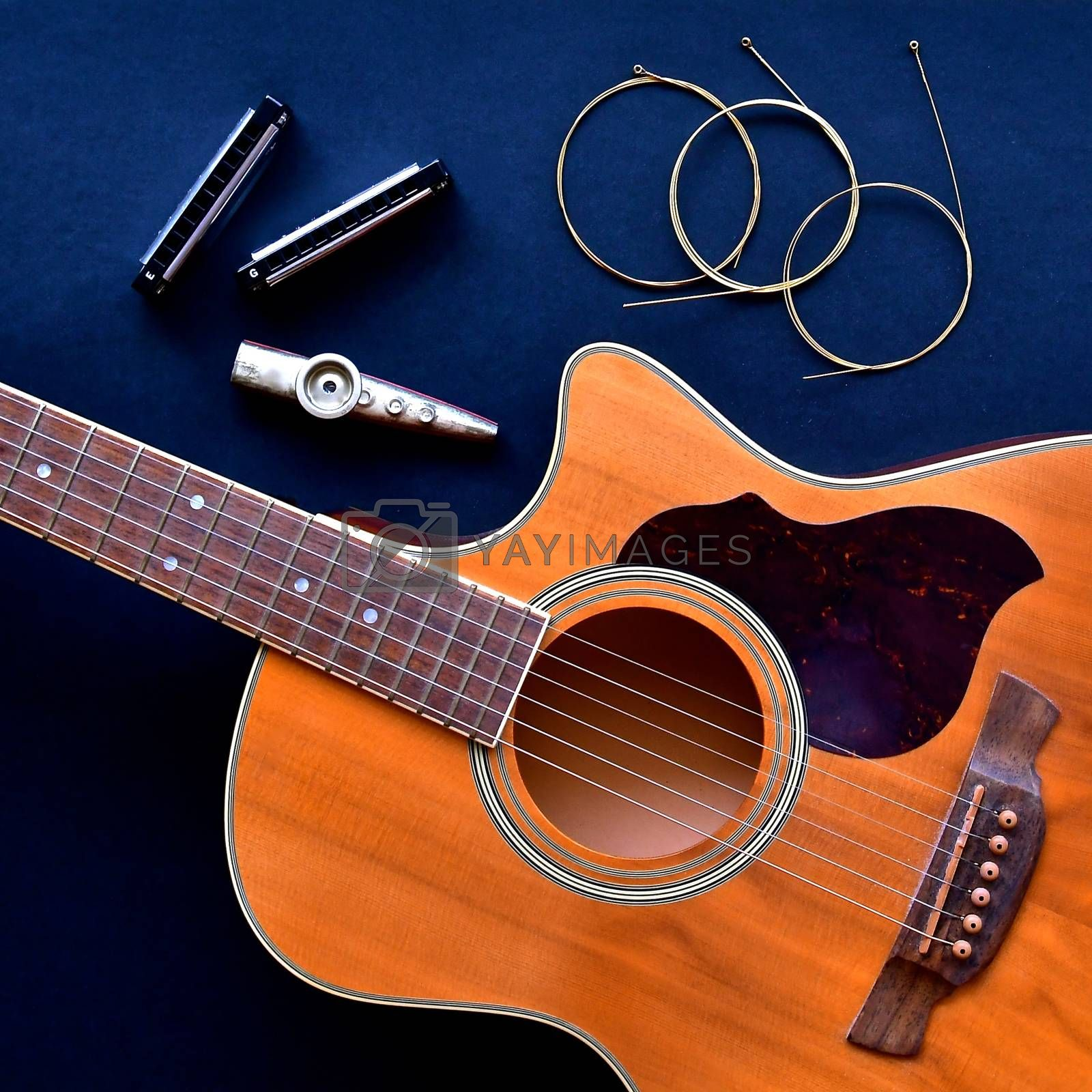 Flatlay view of an acoustic guitar on a black background.