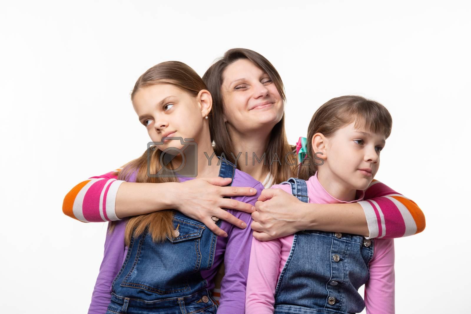 Mom happily hugs children, children turned away from mom