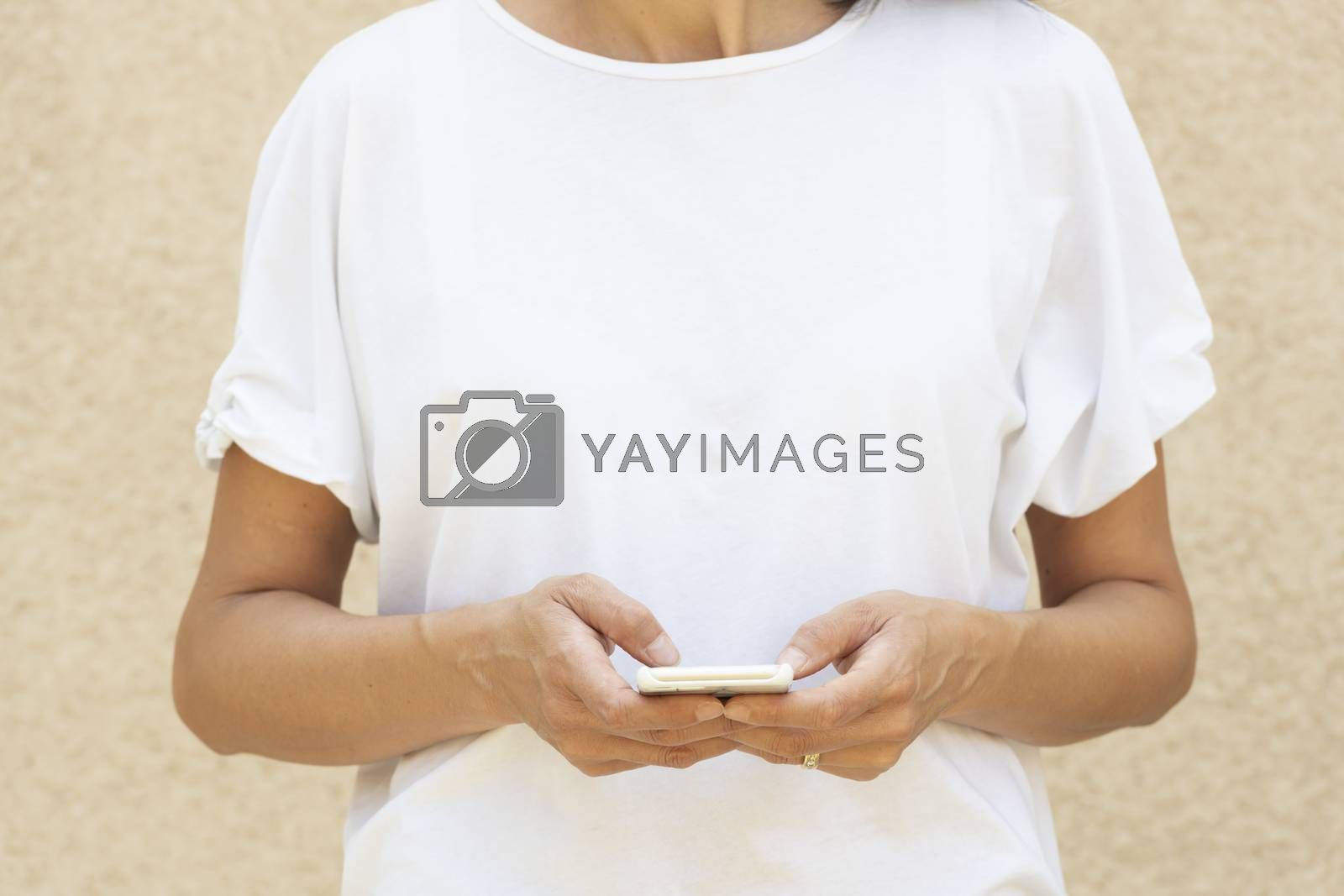 Woman in the forty's using a smartphone with white t-shirt for background or presentation and with large copy space