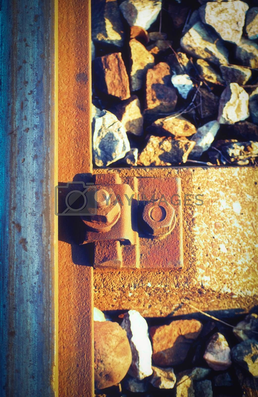 Close up and macro outdoor view of a rusty bolt and screw nut next to a rusty rail steel beam and stones next to the railway.