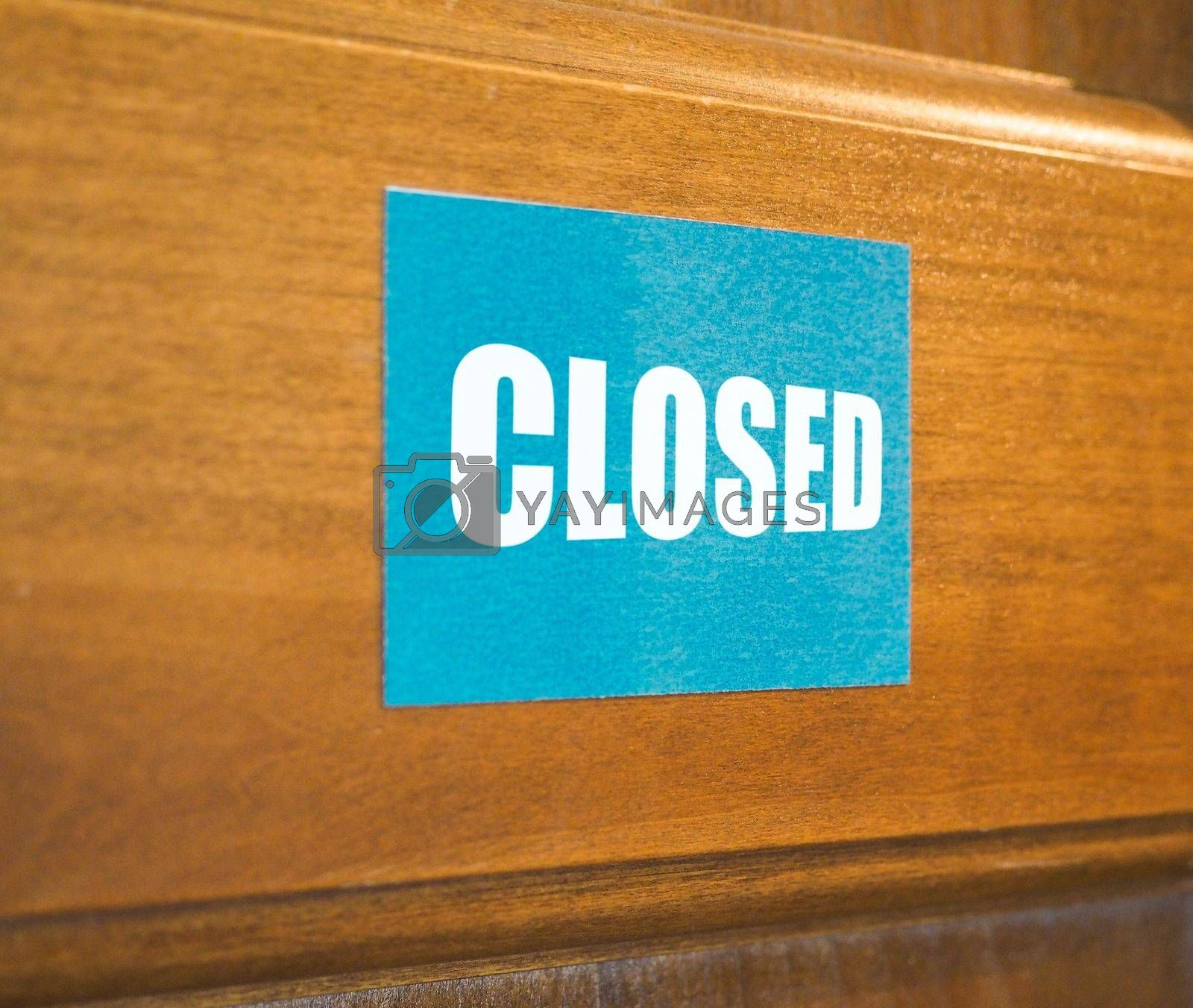 Closed sign on a wooden door, perspective view