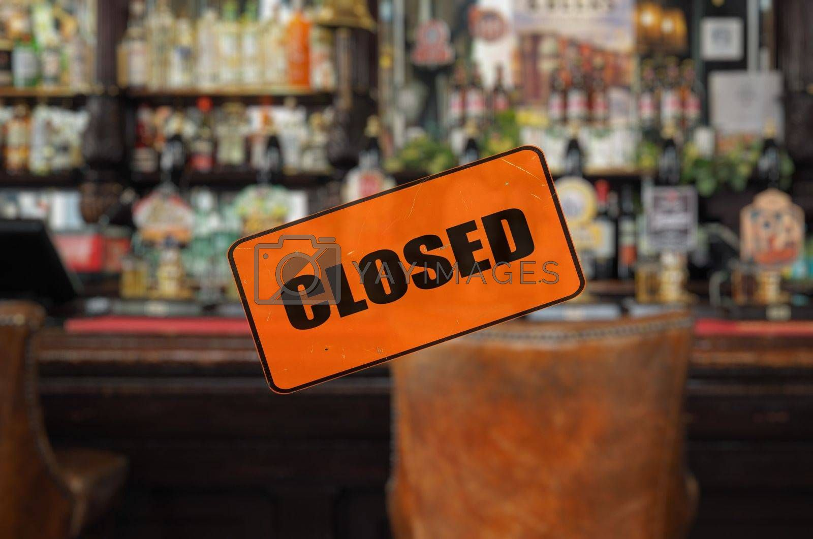 Empty pub, closed sign, focus on foreground with blurred background
