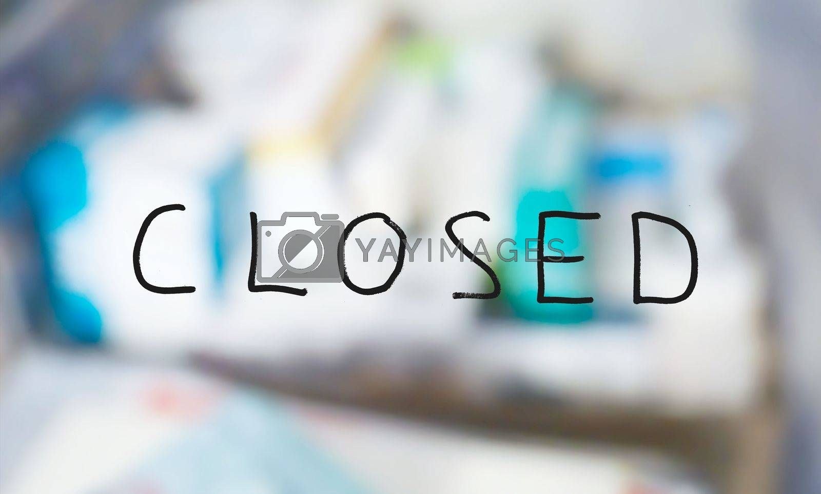 Handwritten closed sign on a shop window with blurred products in the background