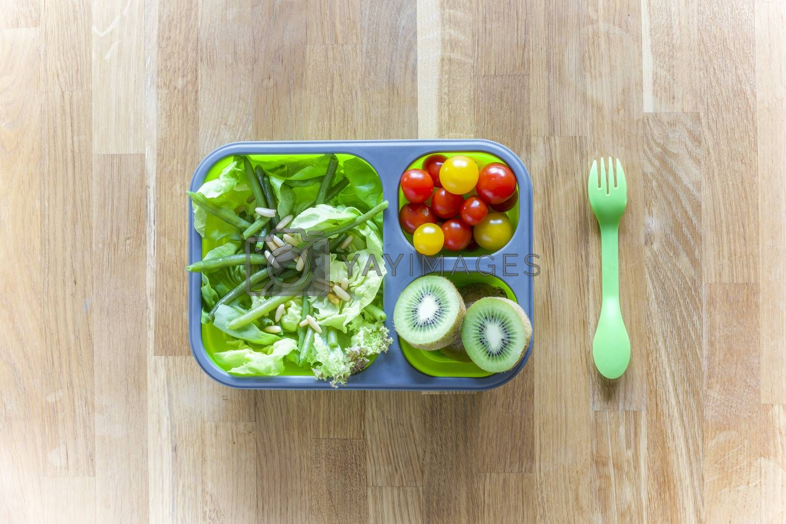 Collapsible silicon lunch box with food (green salads, tomatoes, kiwi) on wooden table
