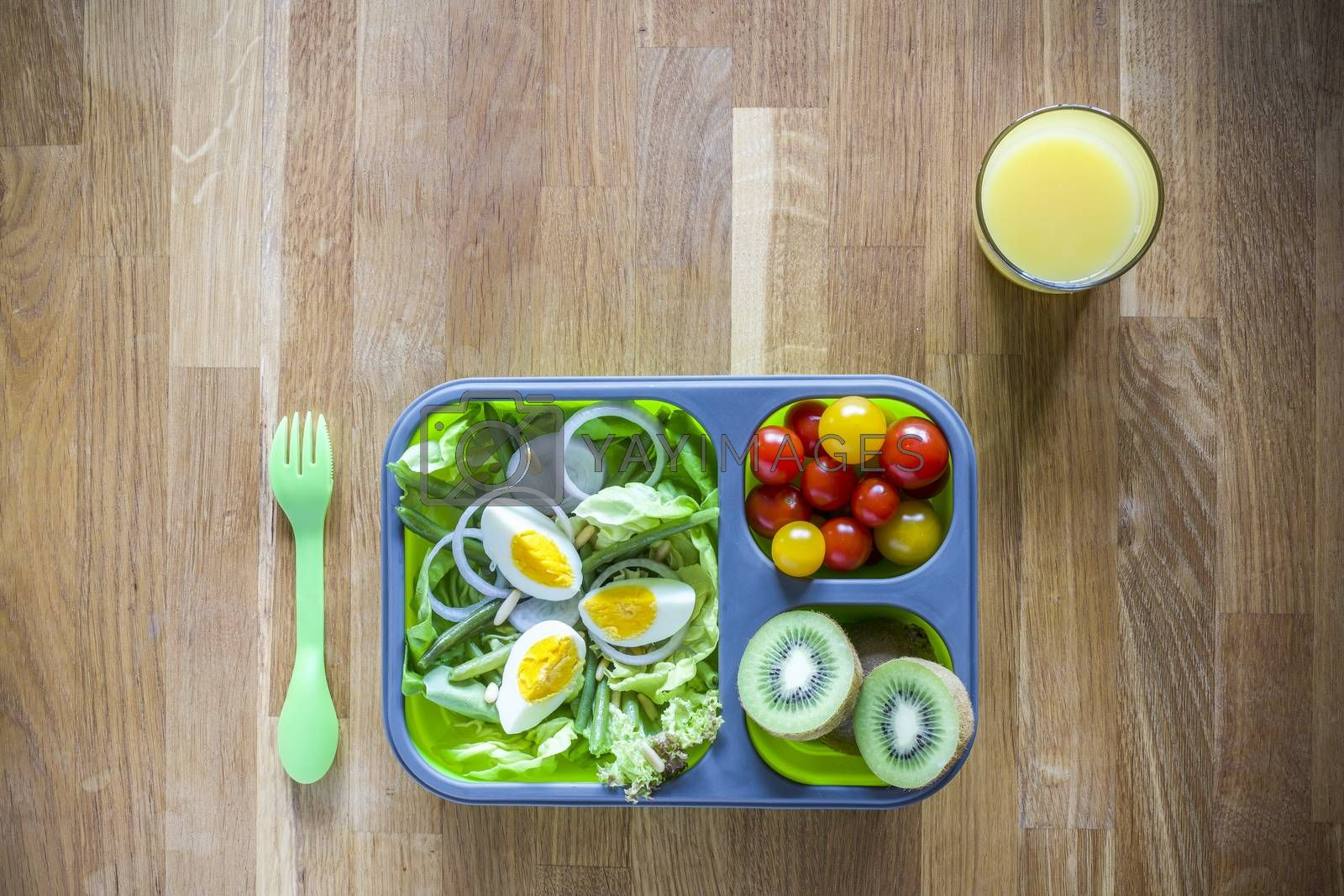Collapsible silicon lunch box with food (salads, eggs, kiwi) on wooden table and orange juice