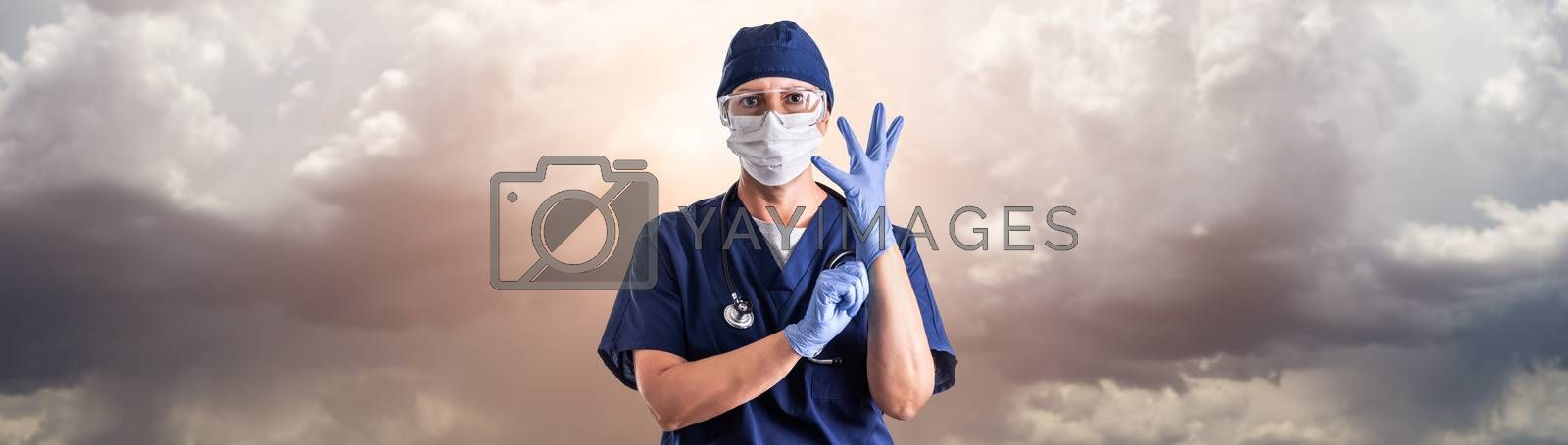 Doctor or Nurse Adjusting Surgical Gloves Wearing Personal Protective Equipment Over Ominous Clouds.