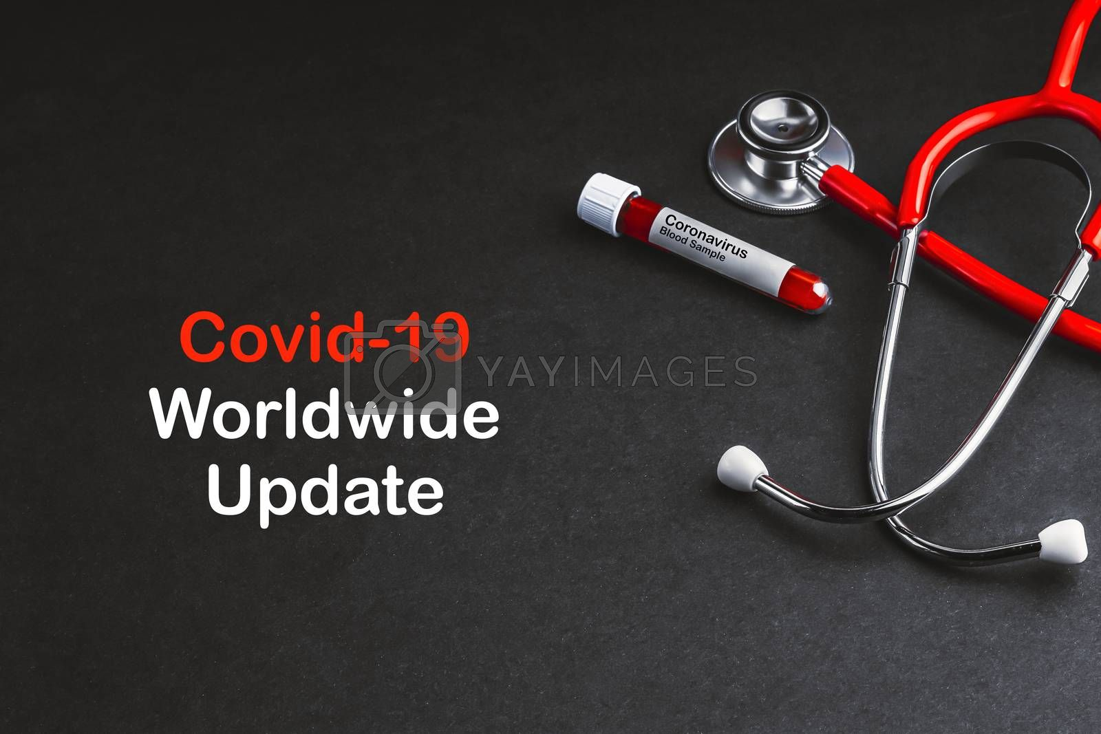 COVID-19 WORLDWIDE UPDATE  text with stethoscope and blood sample vacuum tube on black background. Covid or Coronavirus Concept