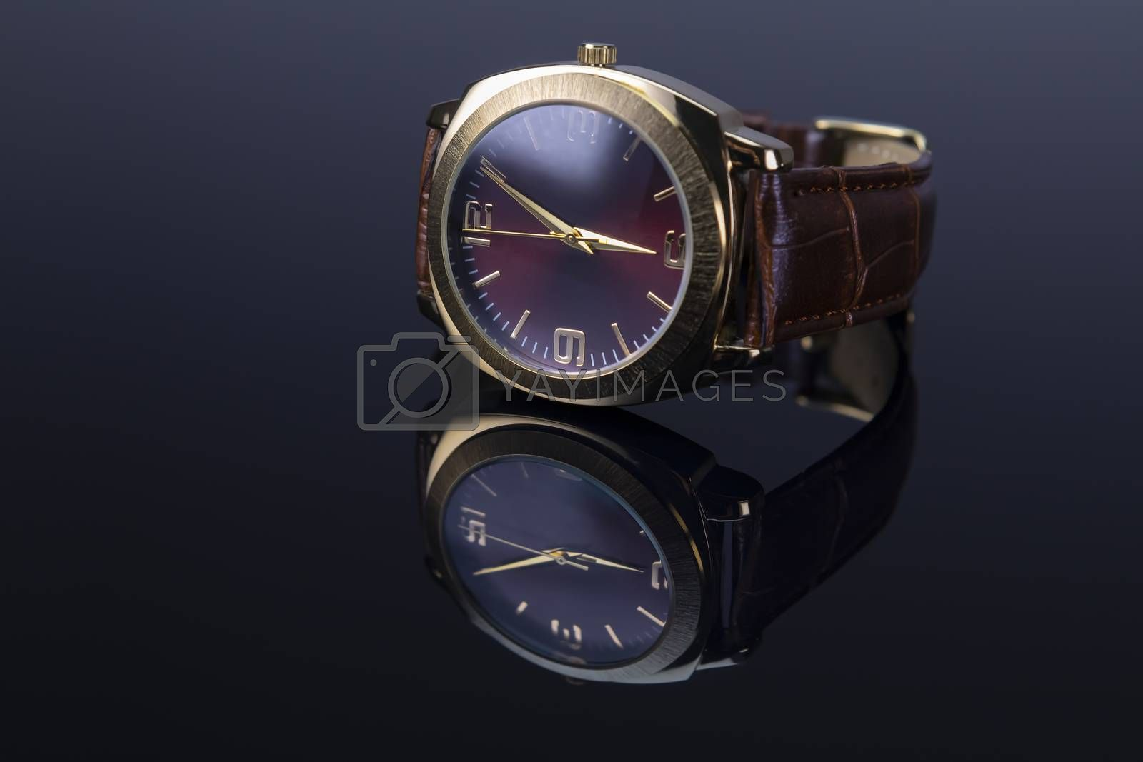 Men watch with leather bracelet on black glossy background. Focus on 9 a clock number.